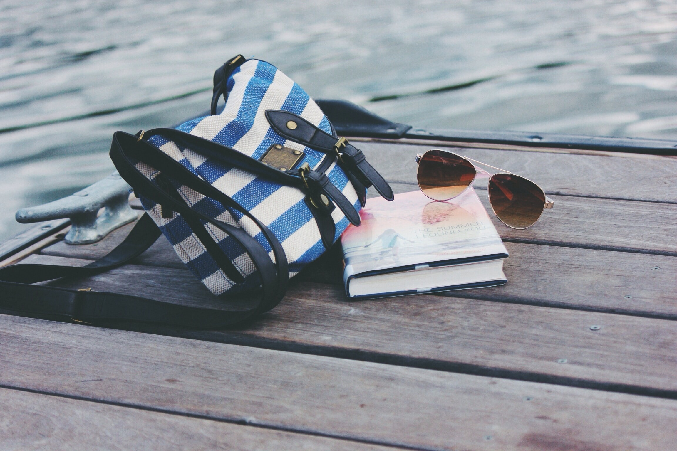 A white-and-blue bag, a pair of sunglasses and a book on a wooden surface