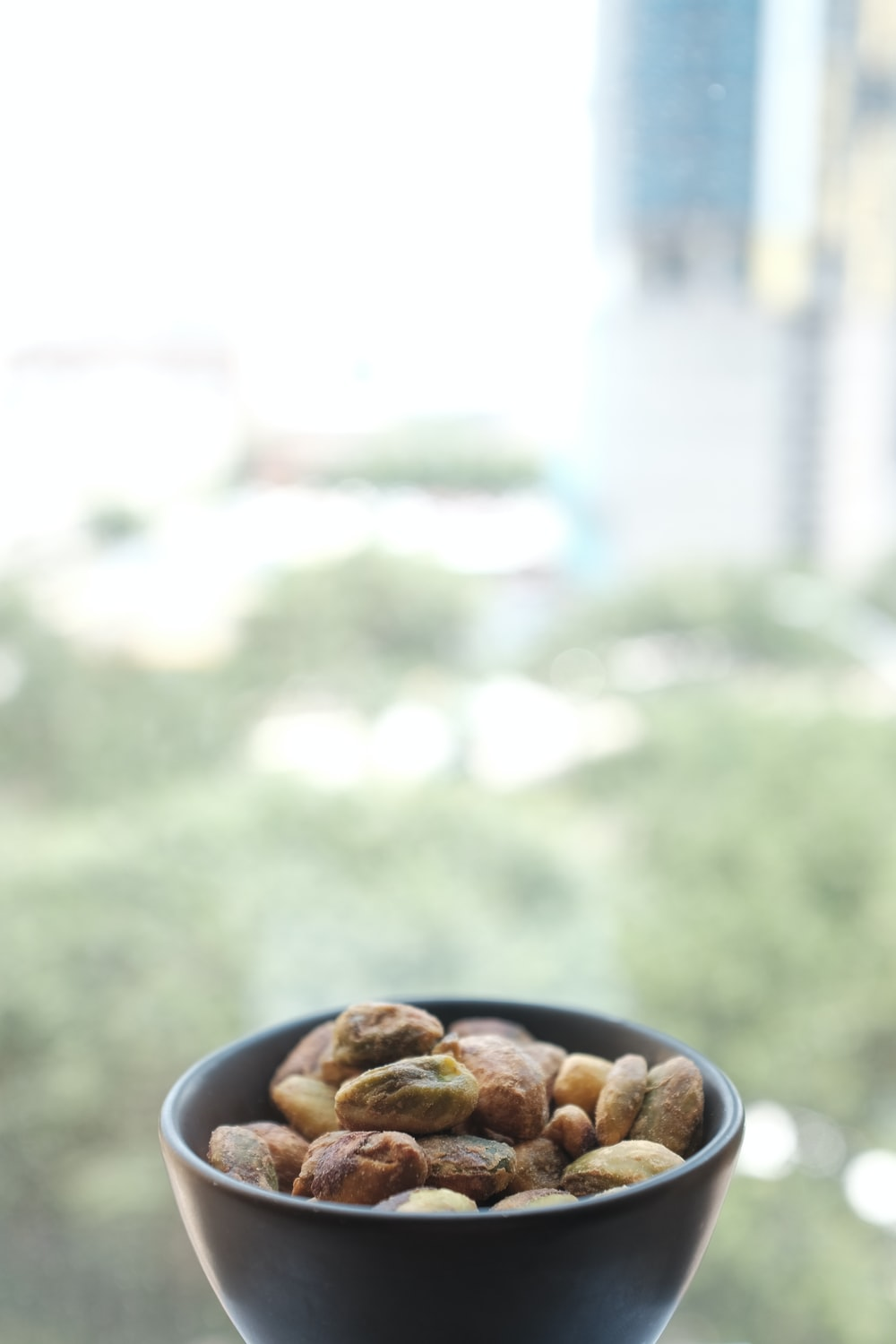 selective focus photography of nuts on black ceramic bowl
