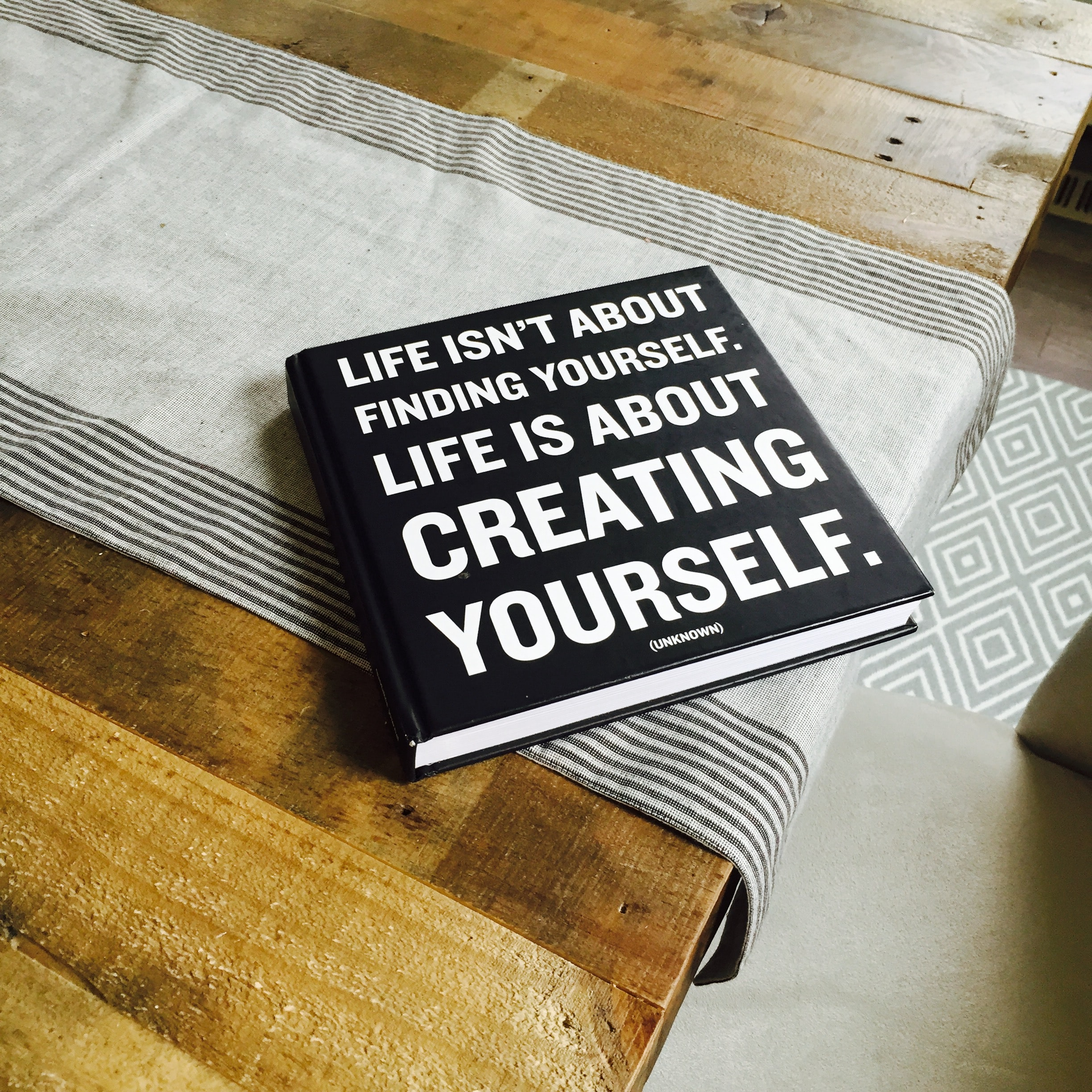 "A black book with the title ""Life isn't about finding yourself. Life is about creating yourself."""