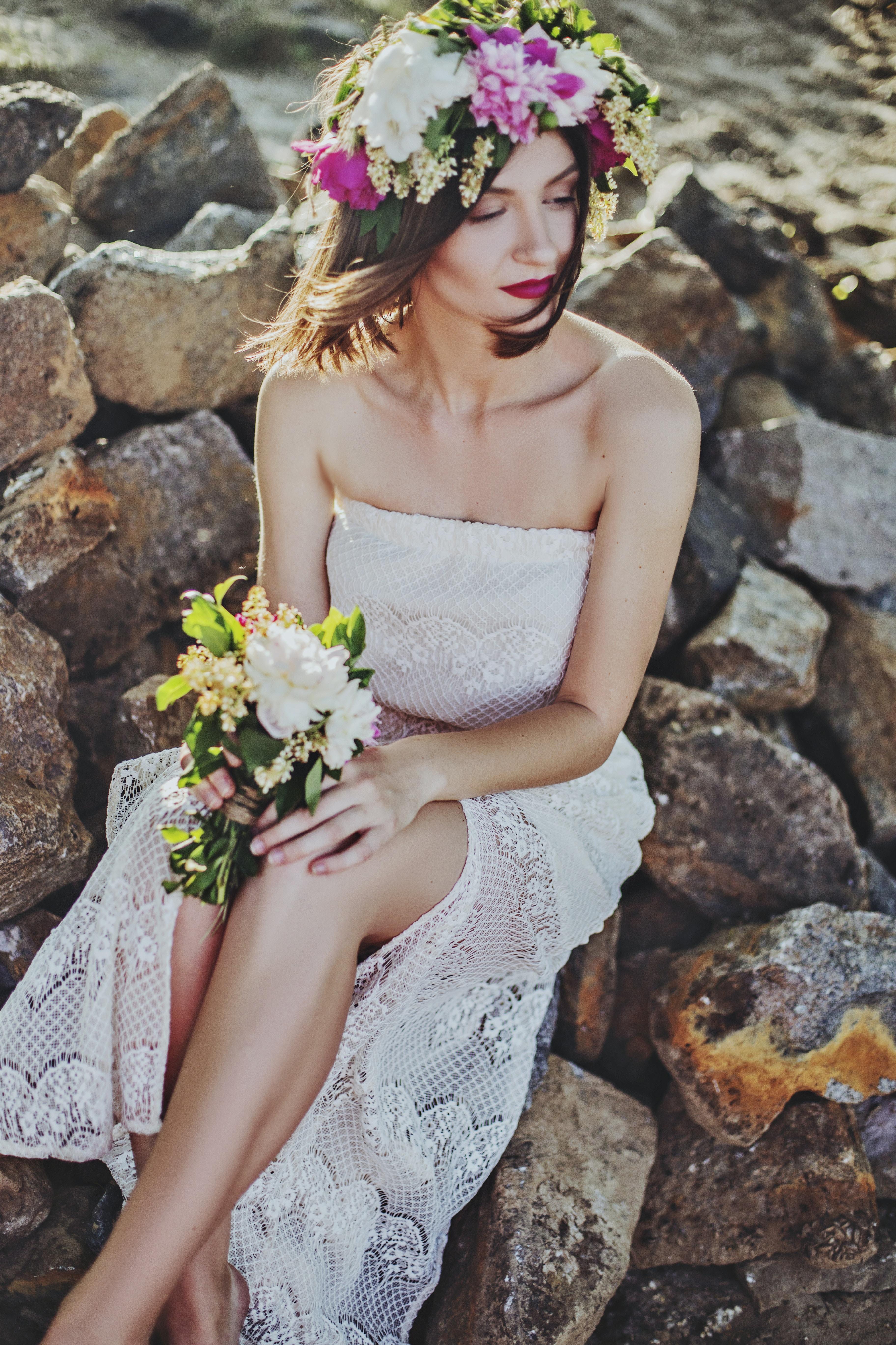 woman in white tube dress sitting on rock