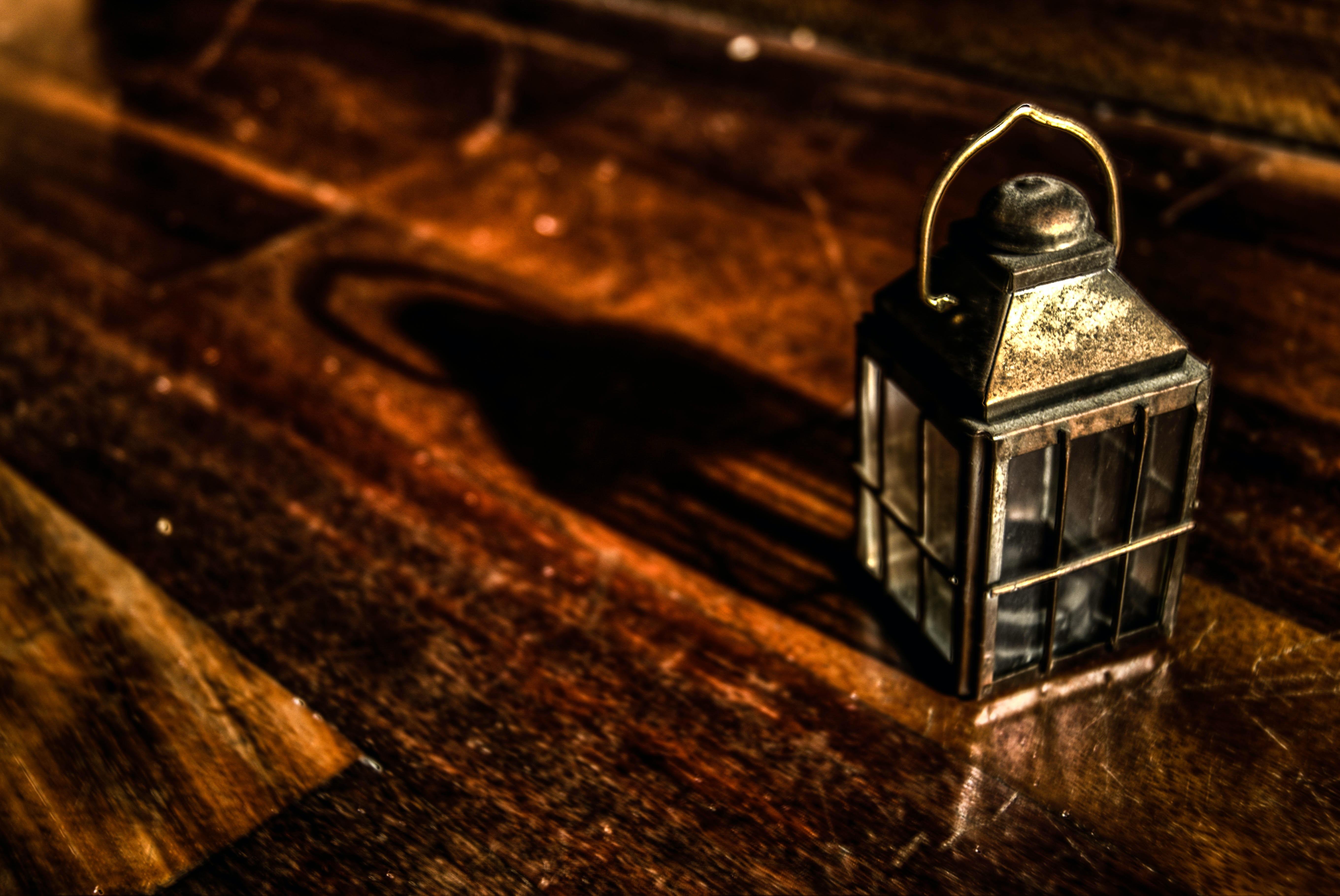 rectangular grey metal candle lantern on brown wooden surface