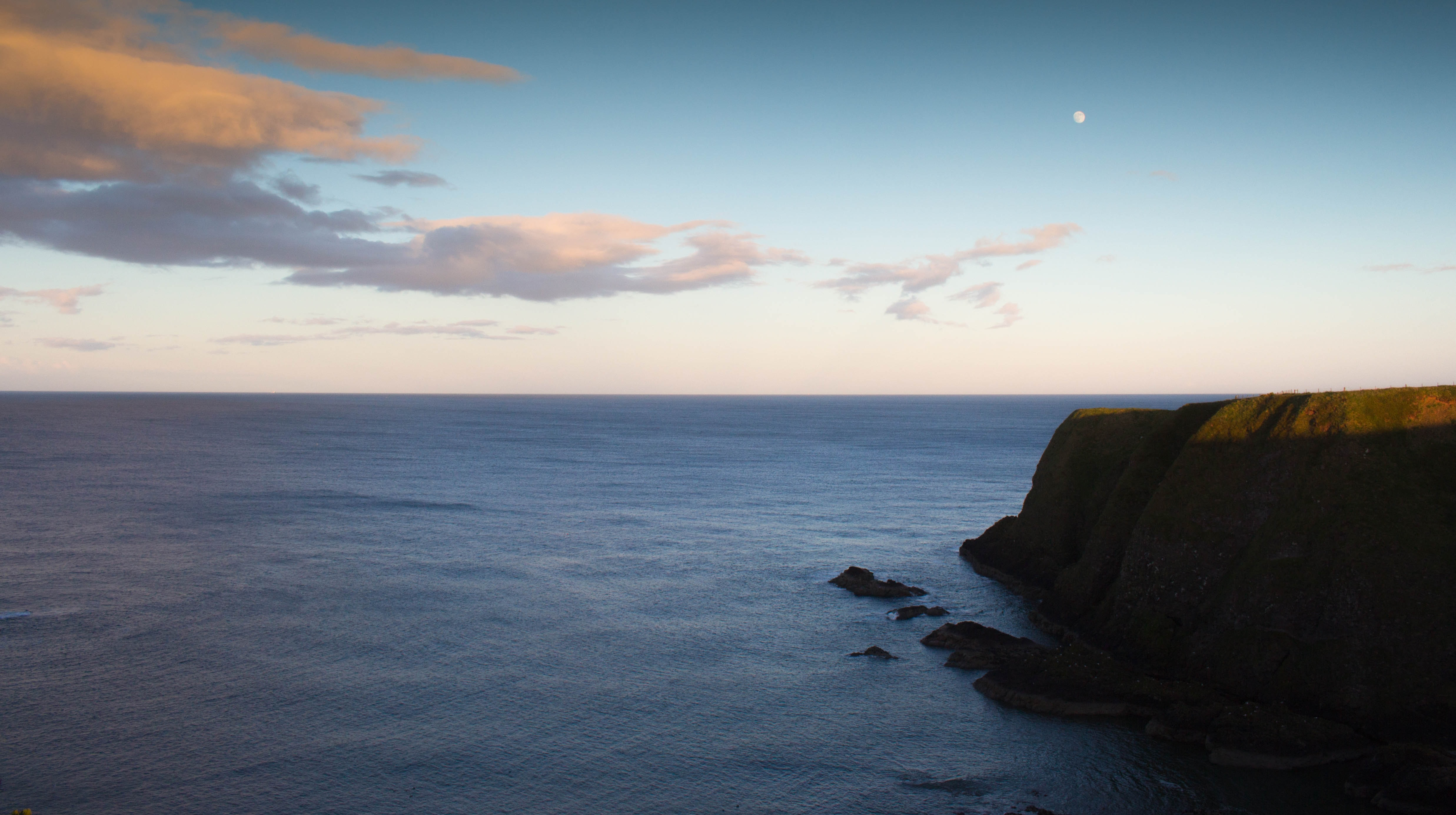 Green cliff above the calm sea with clouds and the moon in the background