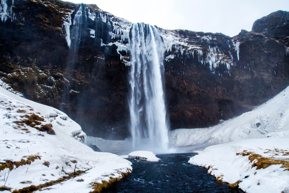 low-angle photography of waterfalls during winter