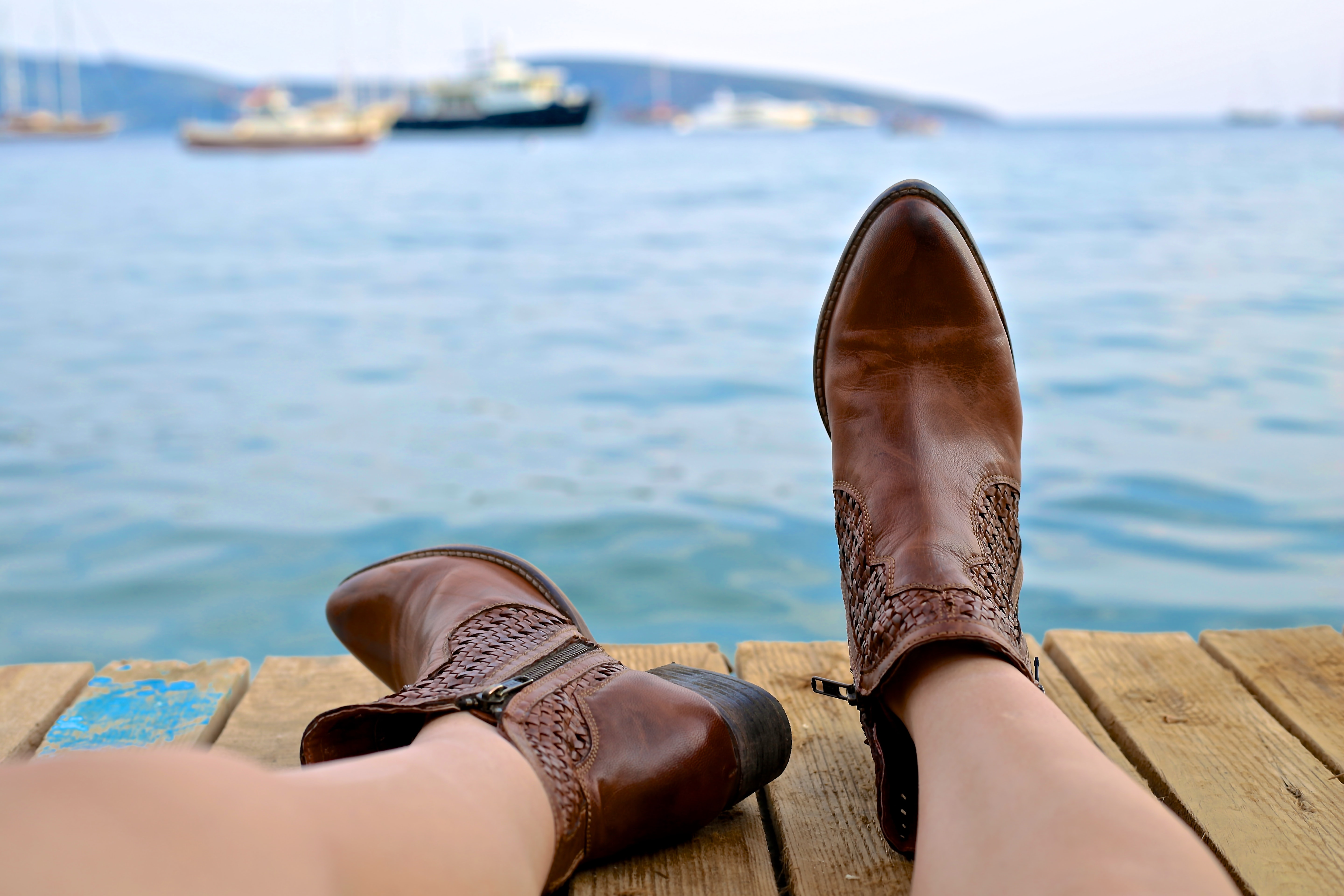 person wearing brown leather side-zip boots sits on brown wooden pier near body of water during daytime