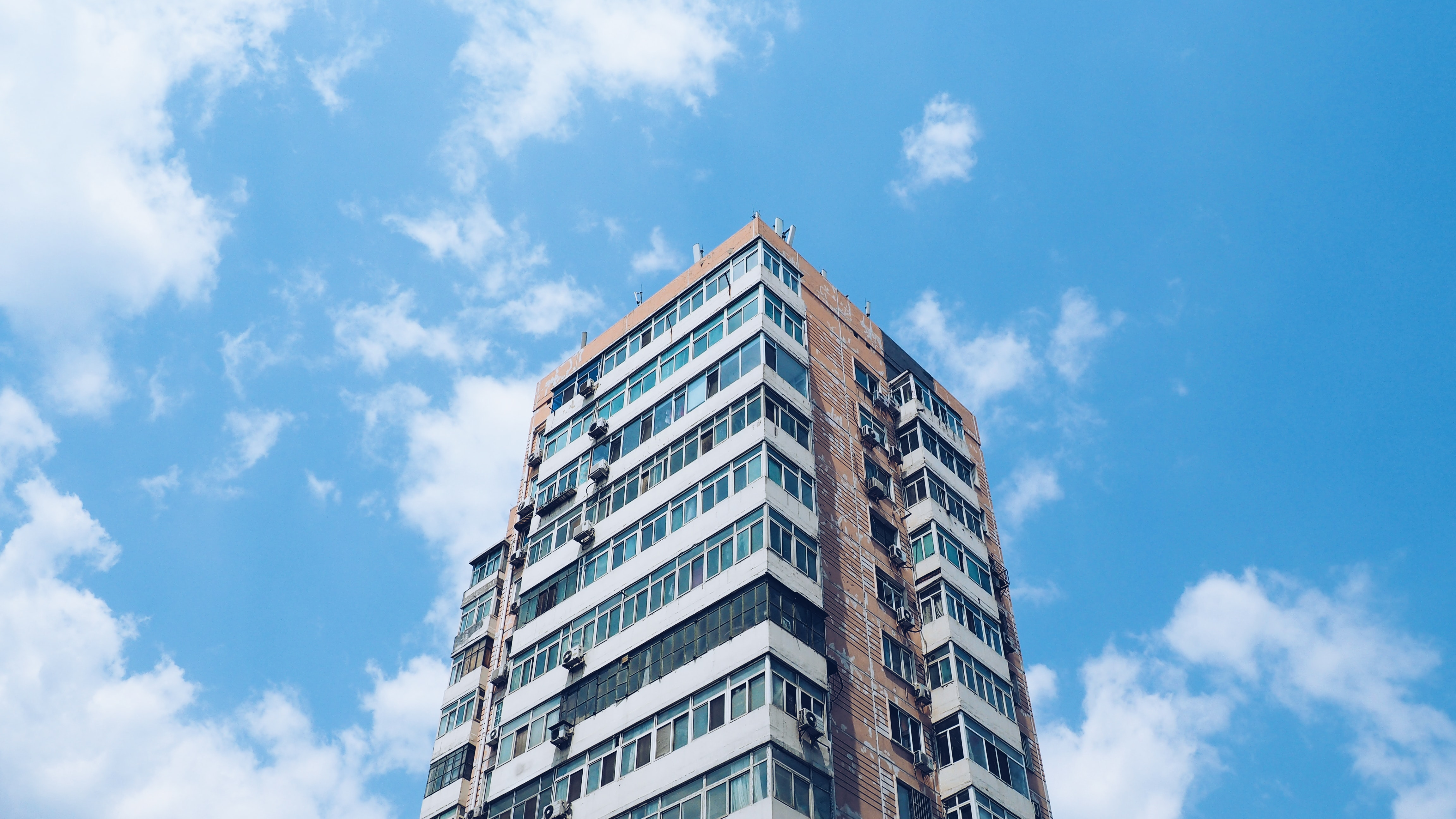 Looking up at a city apartment highrise against a blue sky