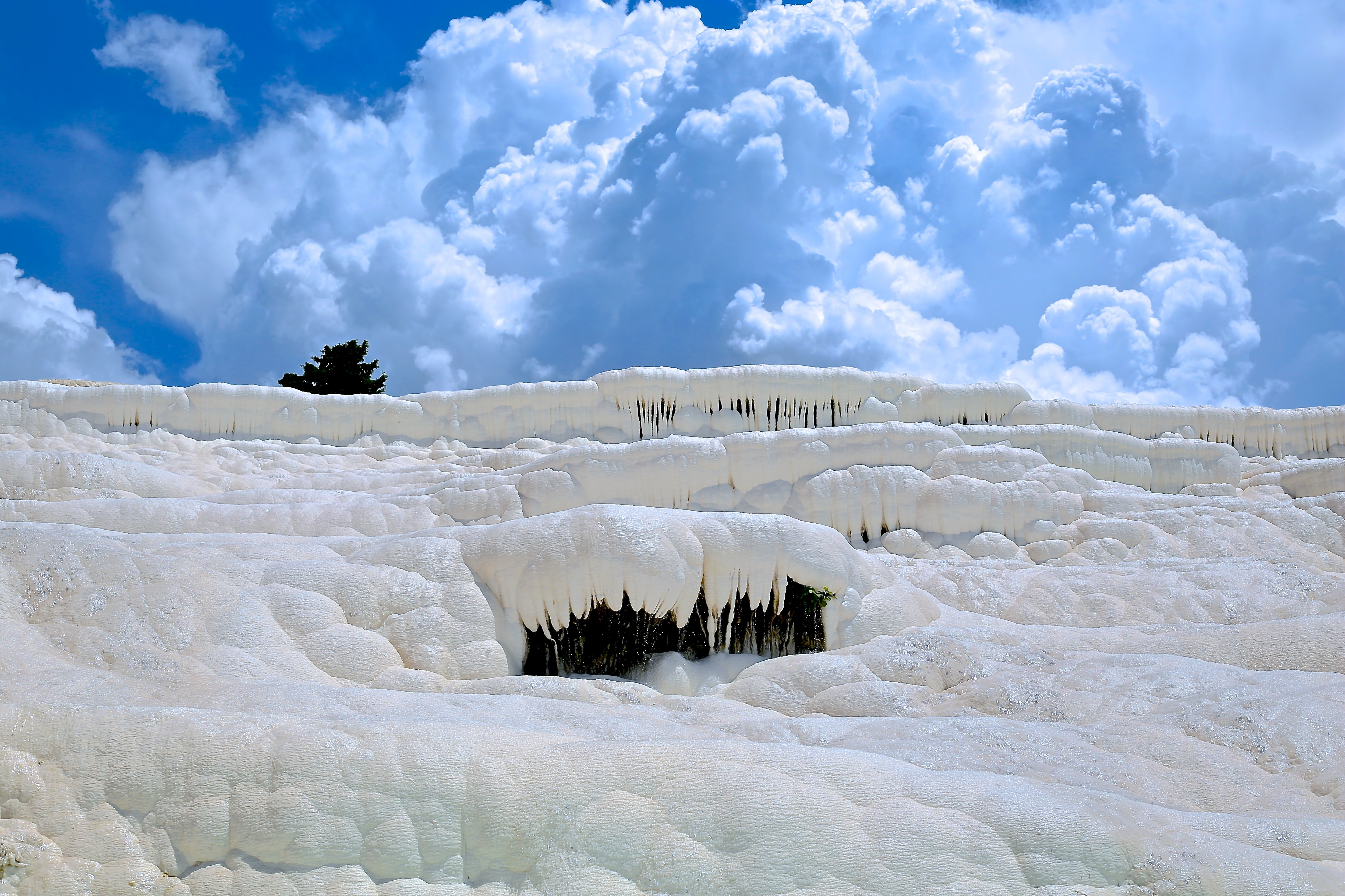 Layers of frozen snow touch blue sky filled with clouds in Hierapolis-Pamukkale