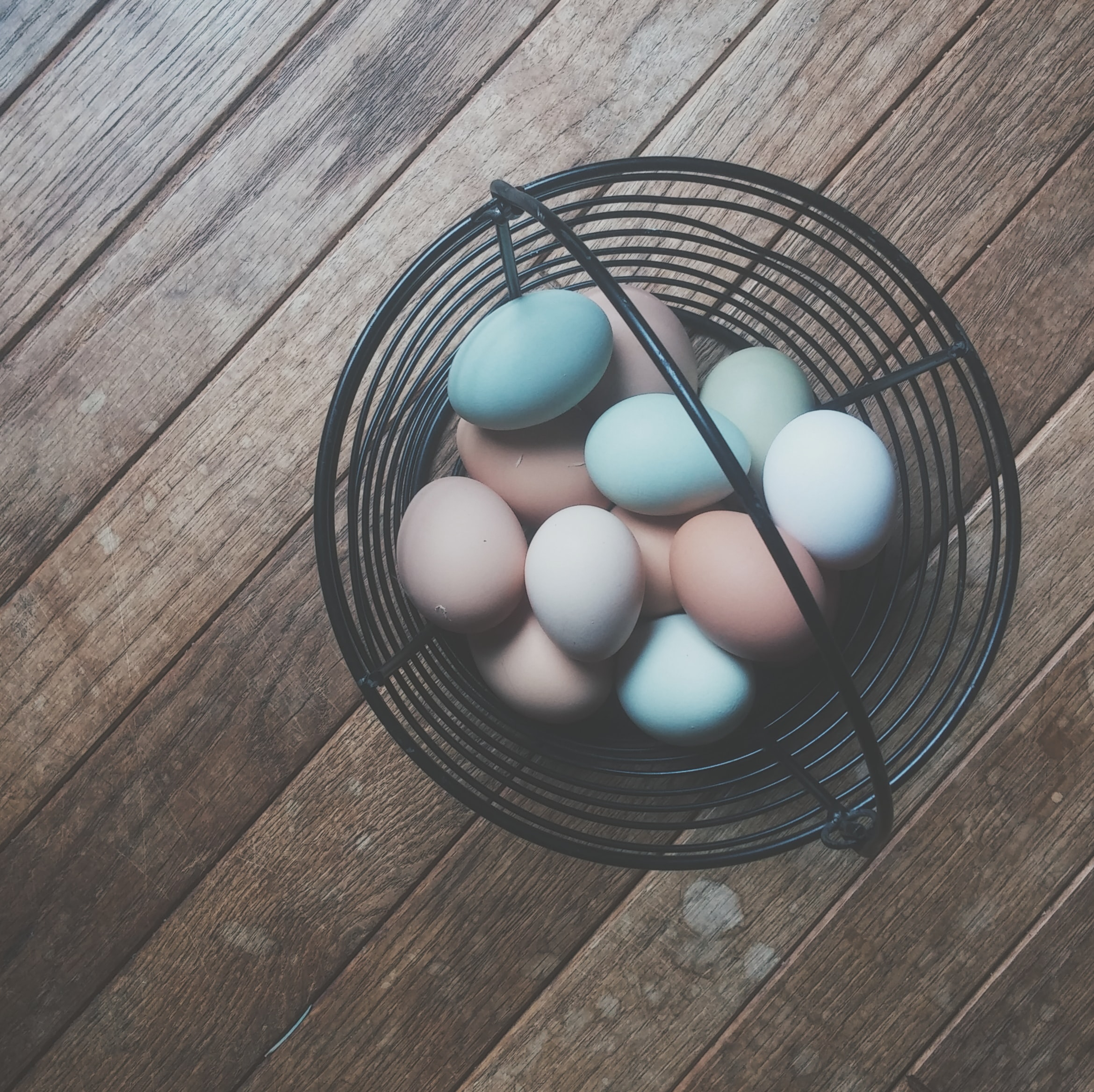 Eggs of different colors are placed in a basket on a wooden panel.