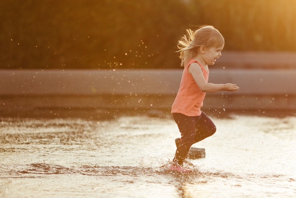 girl in pink tank top and brown shorts running on water during daytime