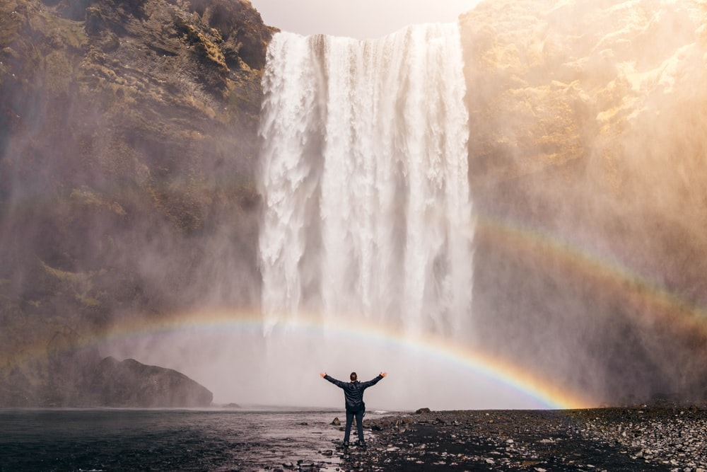 person in front of waterfalls with double rainbow during daytime