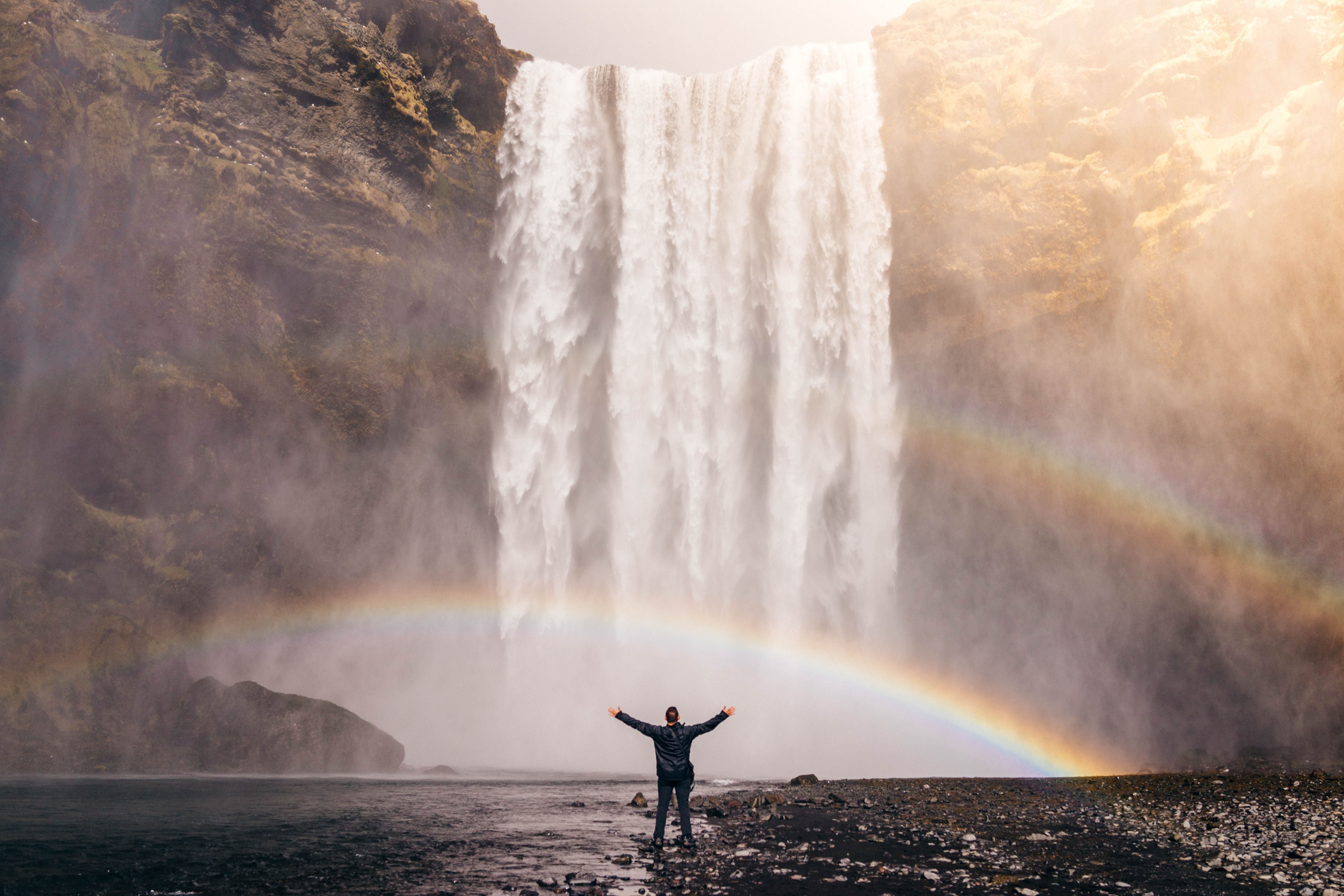 Person standing in front of a waterfall with a double rainbow