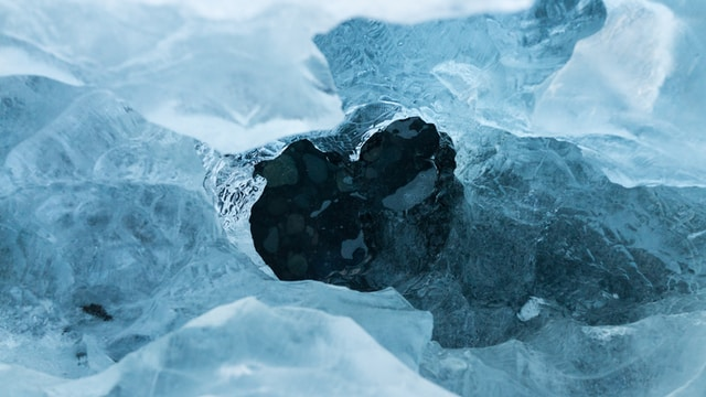 A hole in an ice sheet covering dark blue water