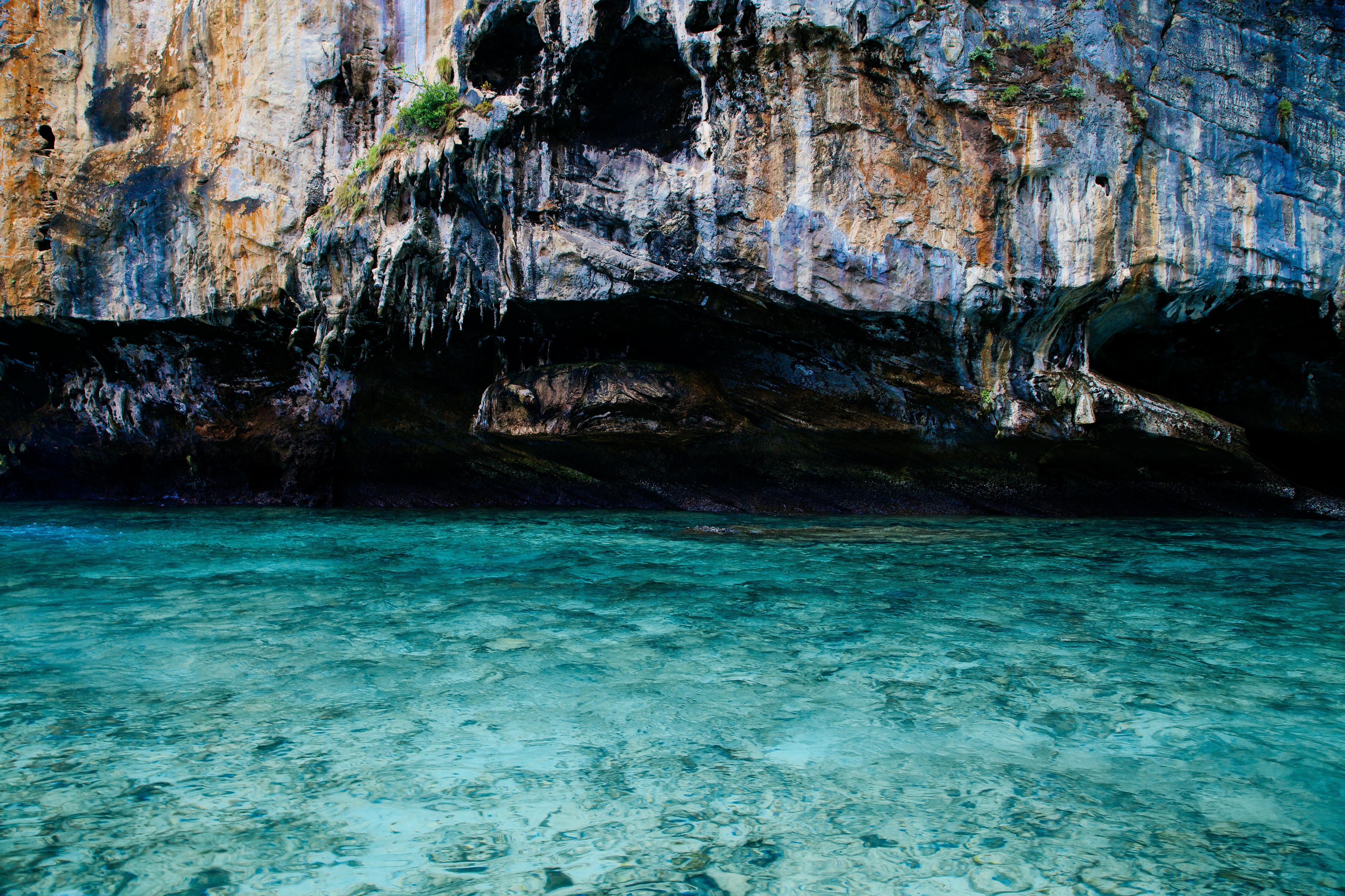 Magnificent blue and green rock face behind azure water