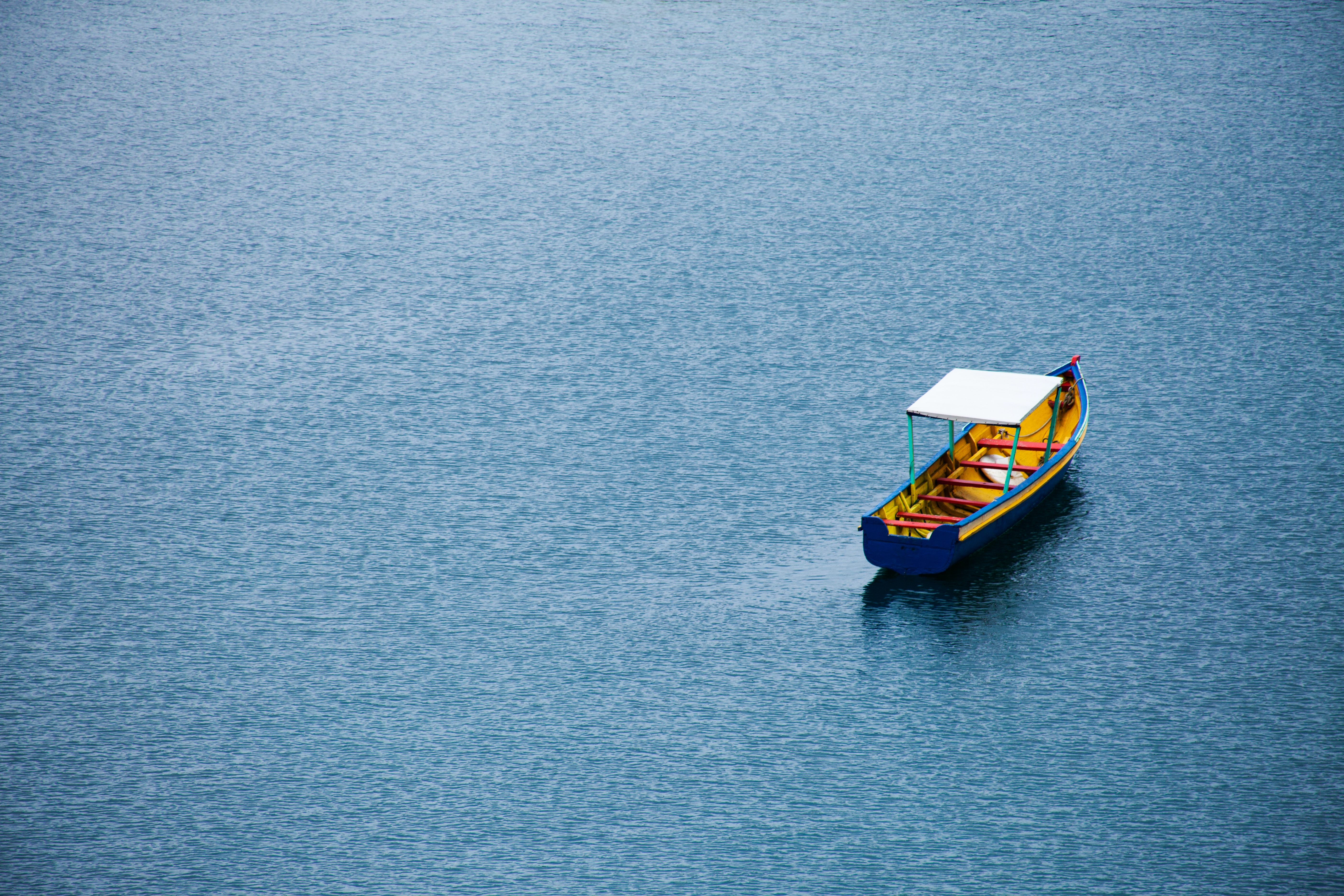 brown and blue boat on water at daytime