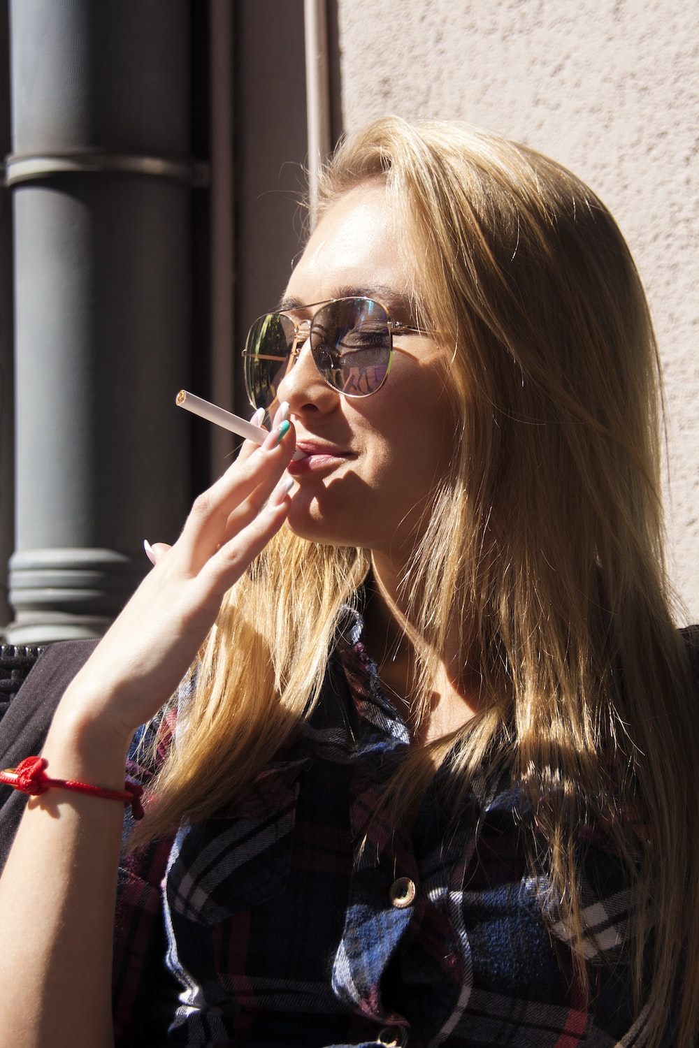 close-up photography of woman holding cigarette stick during daytime