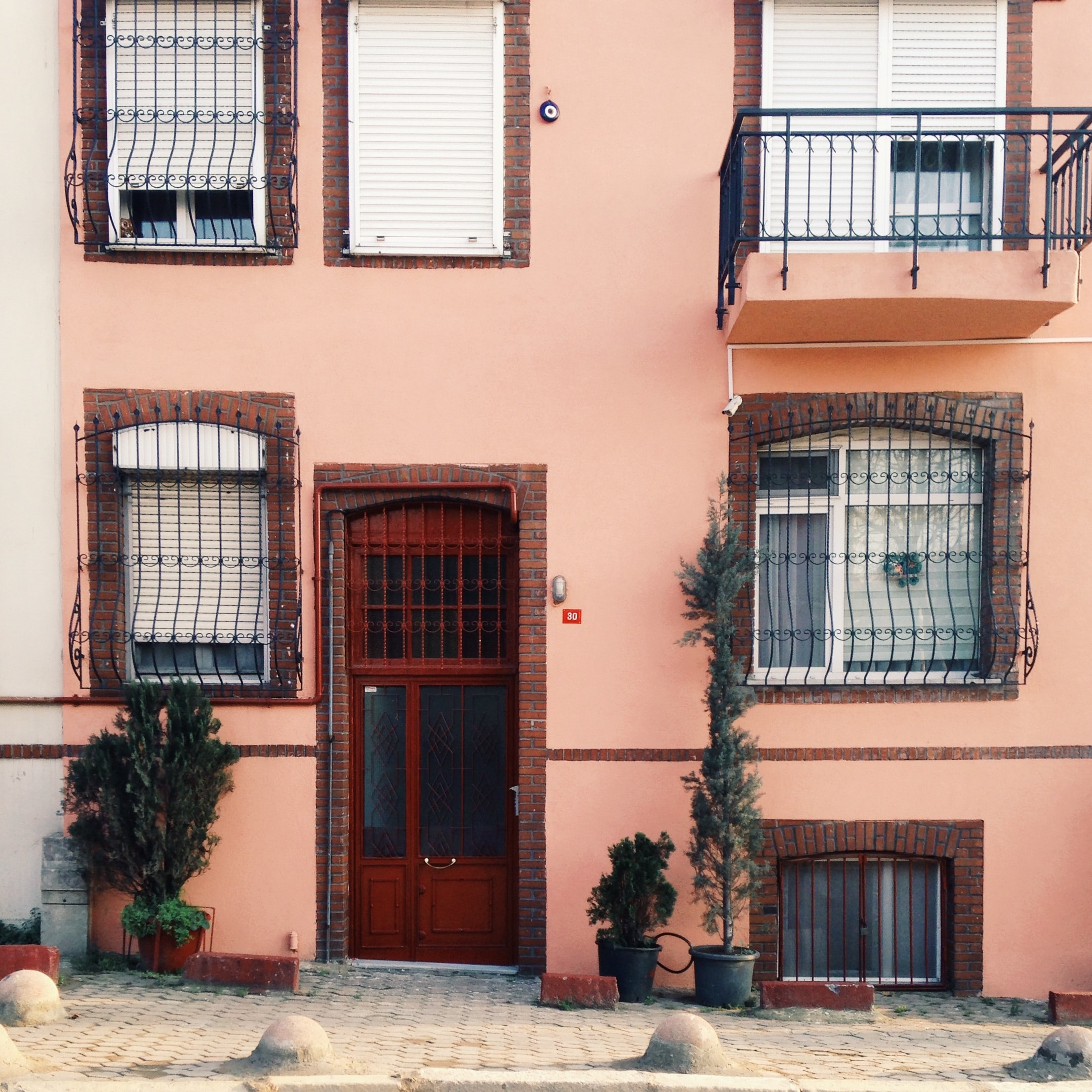 Salmon pink house with red door and barred windows behind cobblestone street