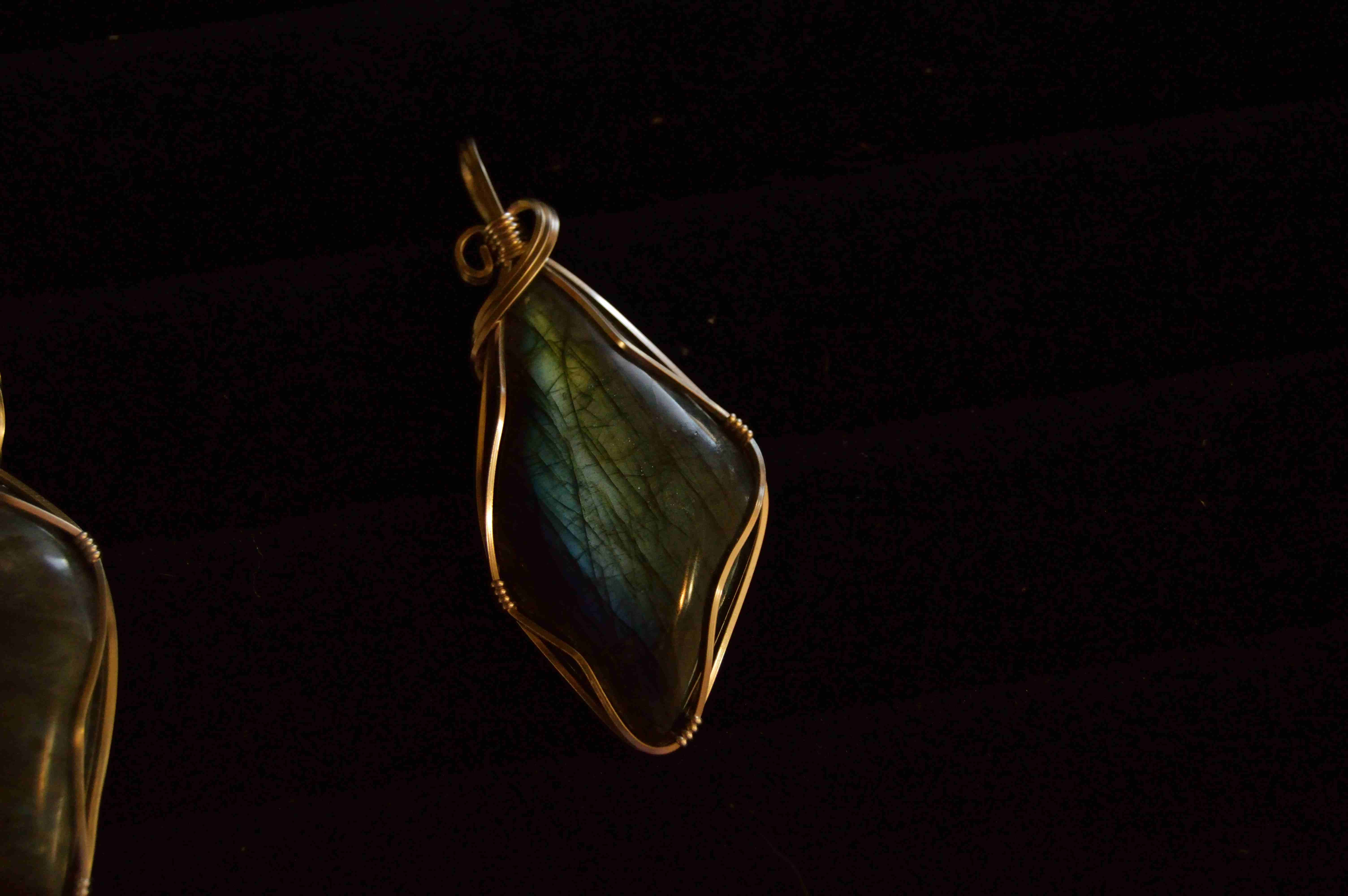 A gemstone pendant wrapped in a copper wire against a black background