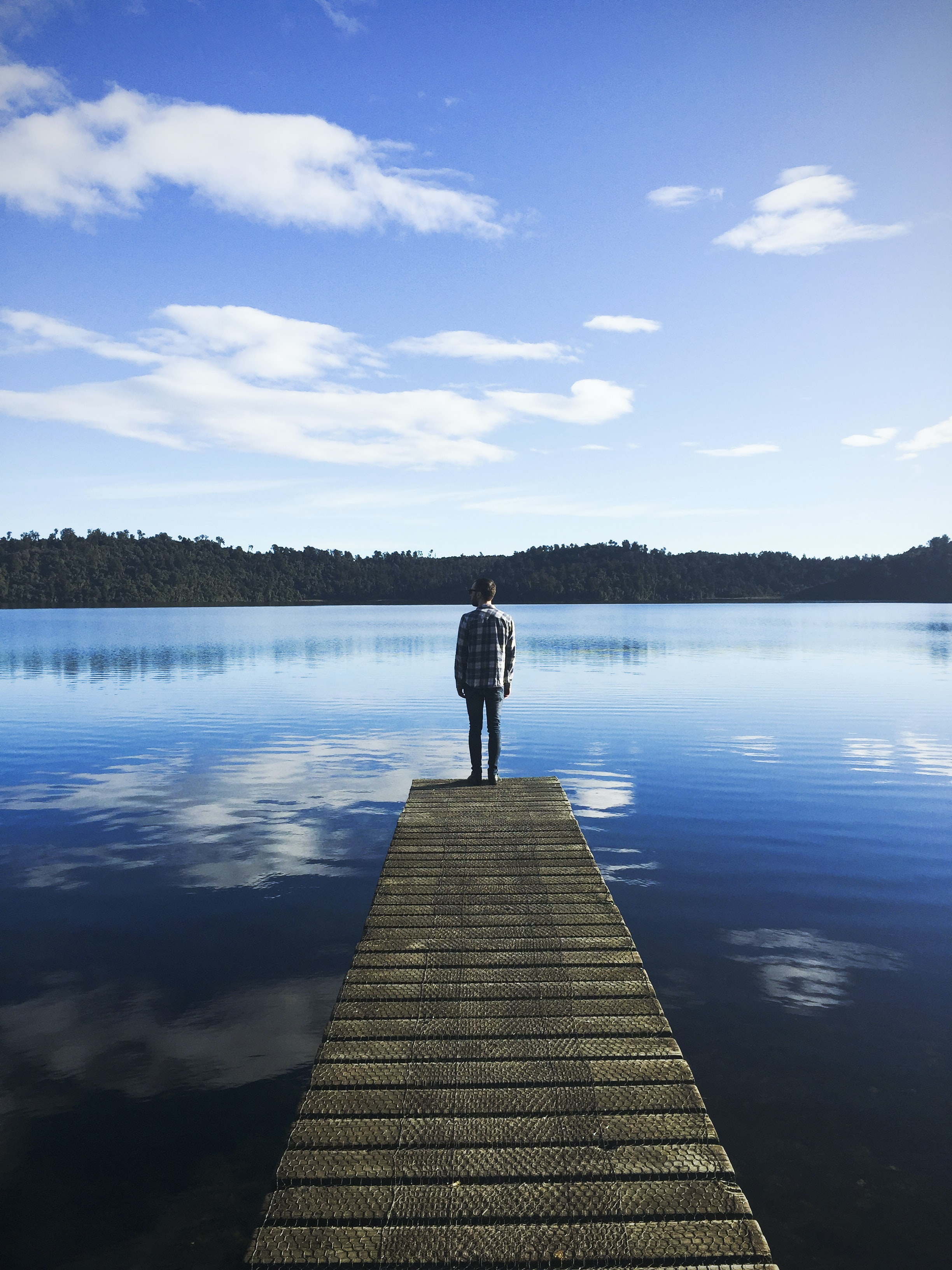 A man wearing a flannel standing on the edge of a dock on a lake that is reflecting the blue sky and clouds