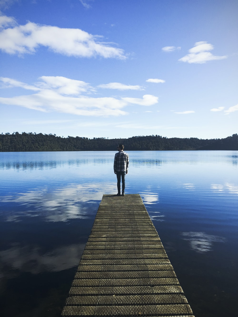 man standing on lake dock watching water under blue sky during daytime