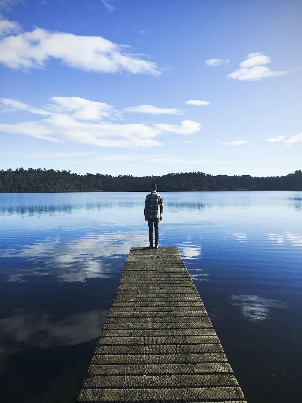 man standing on lake dock watching water under blue sky during daytime