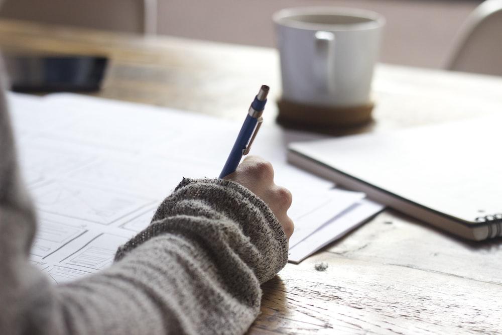 白いセラミックマグの近くの茶色の木製テーブルに書いている人