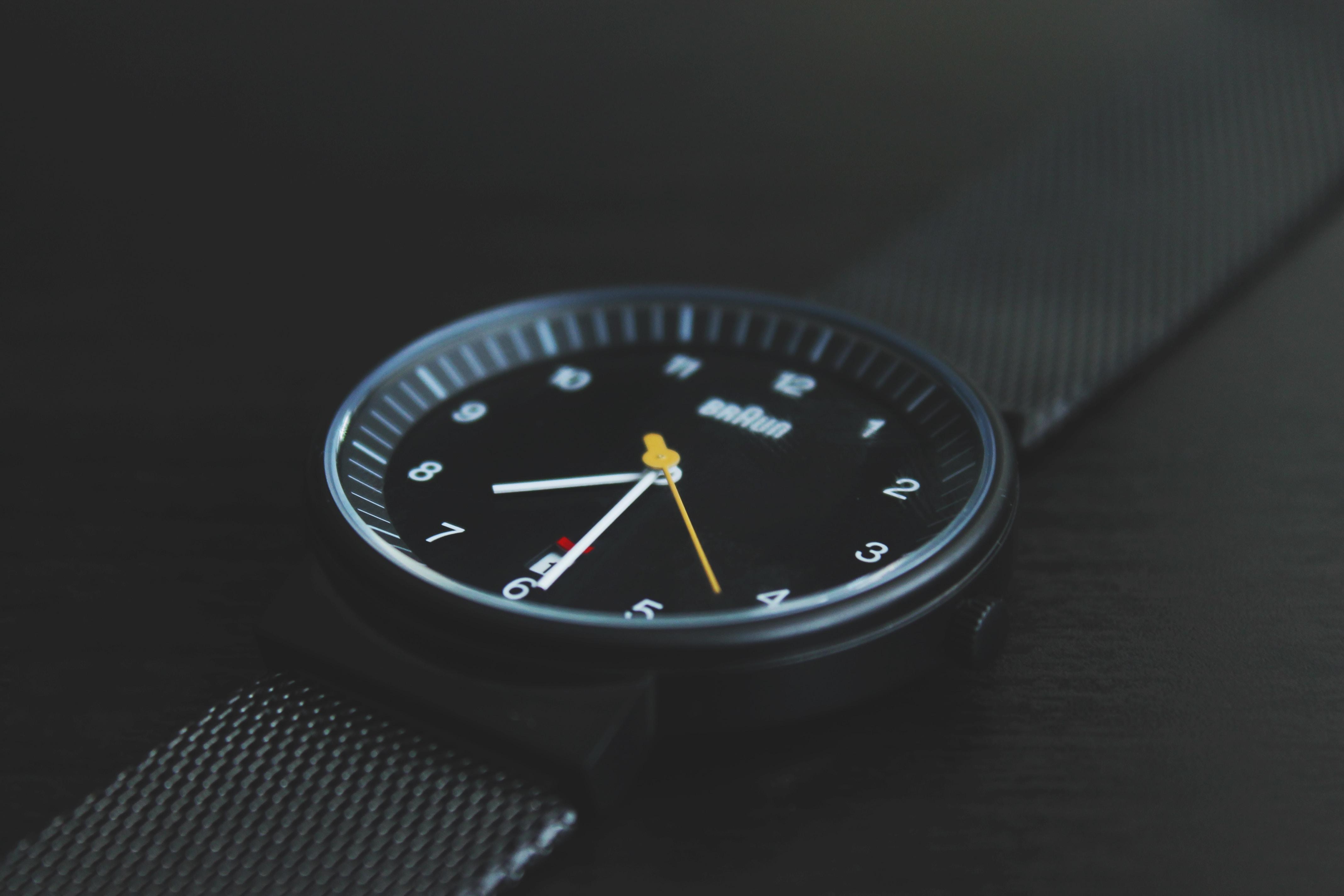round black Braun analog watch with black band at 7:30