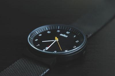 round black braun analog watch with black band at 7:30 watch teams background