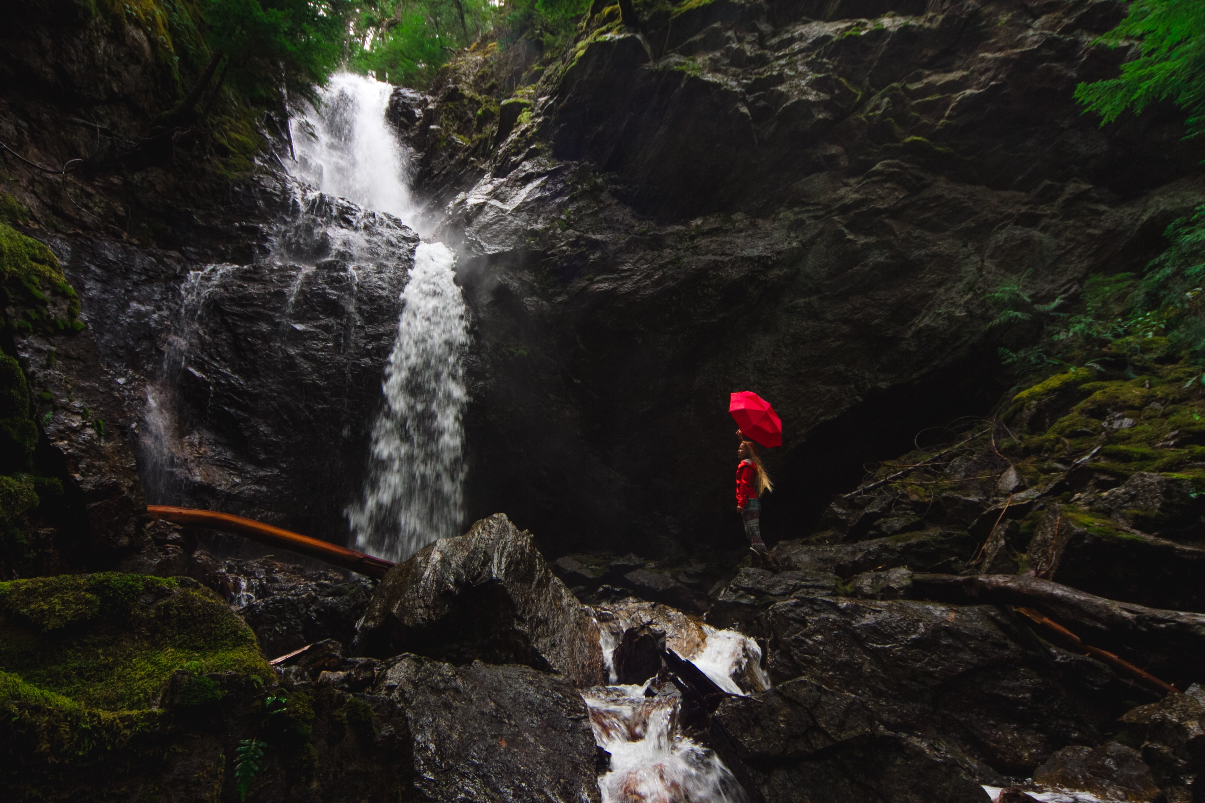 person standing on rock formation under red umbrella beside waterfalls