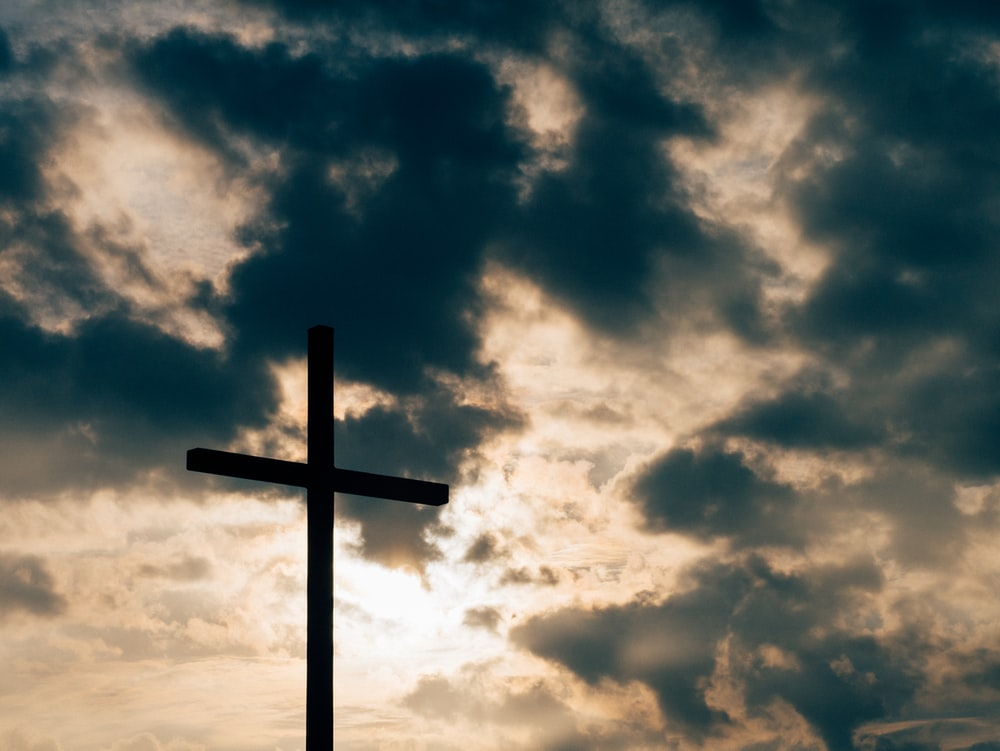 silhouette of cross under cloudy sky