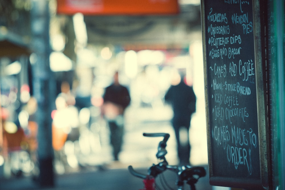 red and gray bicycle parked near black chalkboard with menu writing selective focus photography
