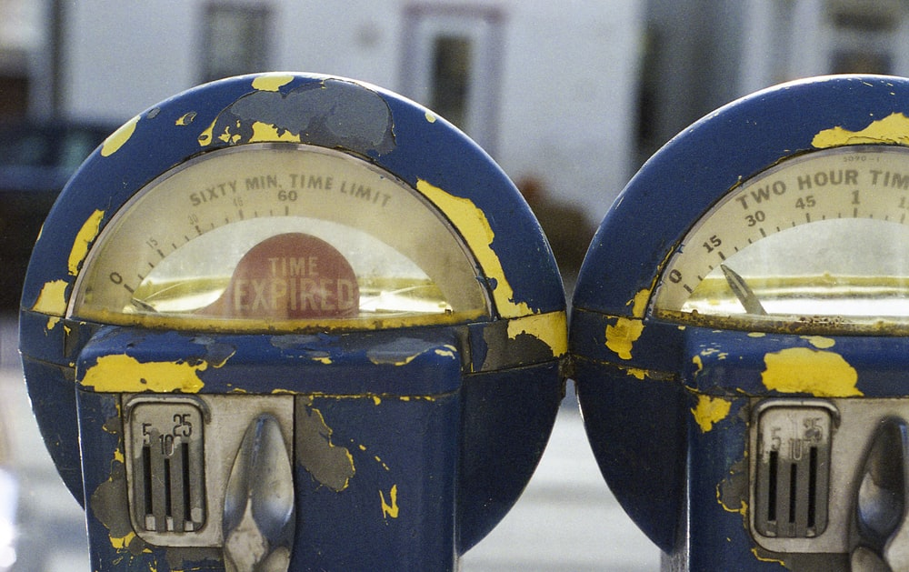 two round blue-gray-and-yellow parking meters
