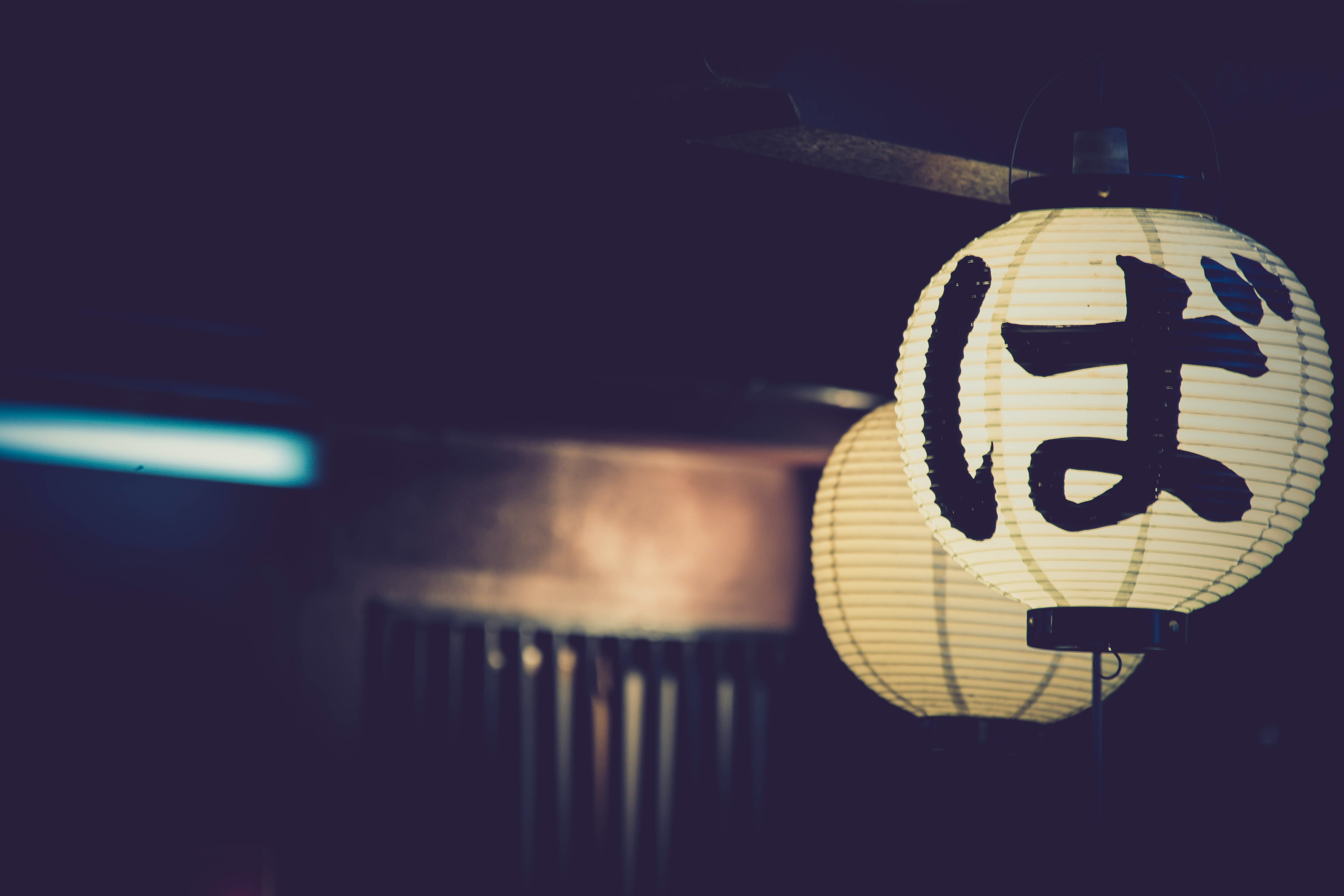 Two illuminated Japanese lanterns in a dark setting by a door