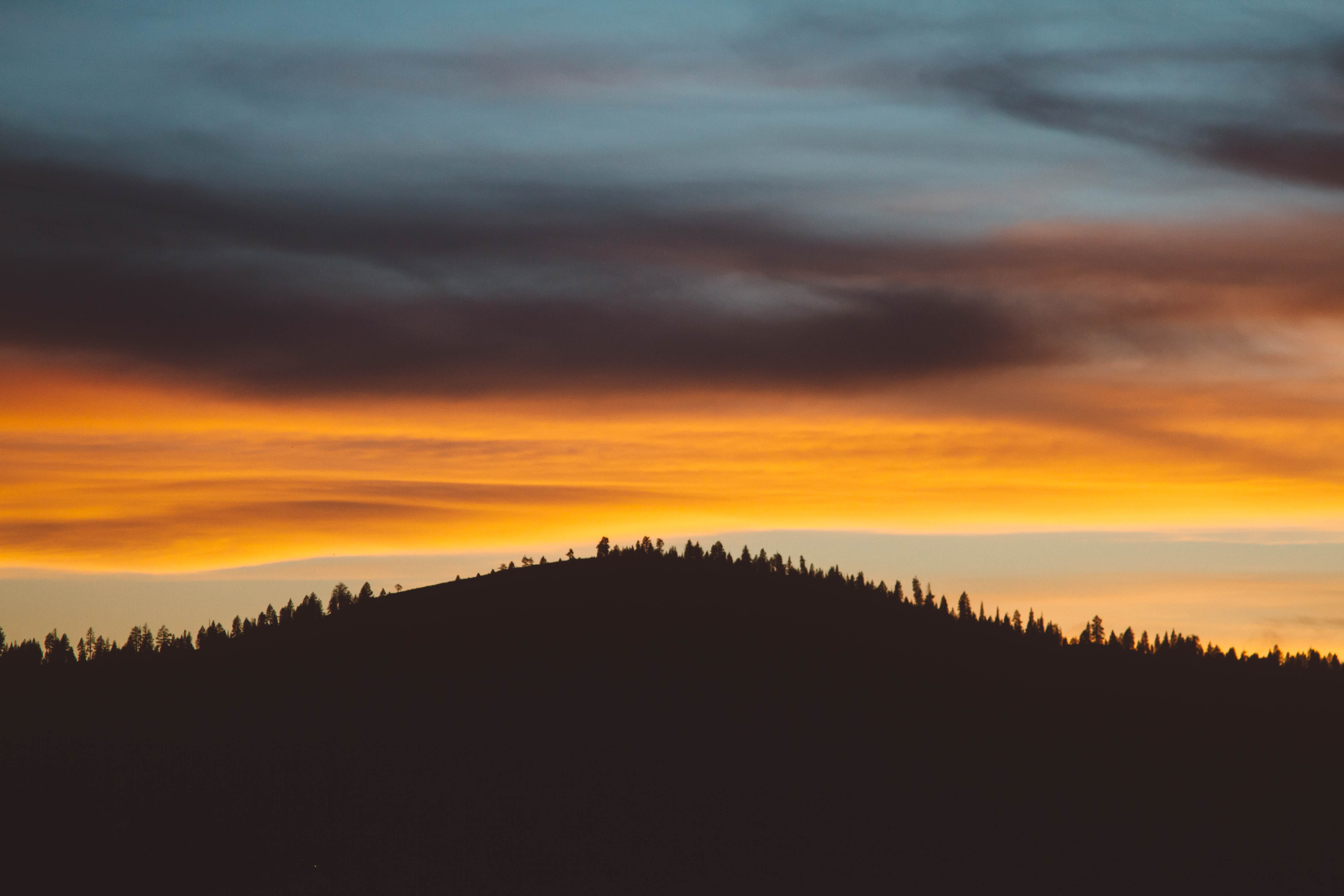 A silhouette of a wooded hill against orange sky during sunset