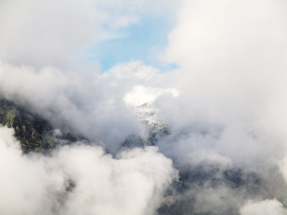white and black mountain covered with clouds at daytime