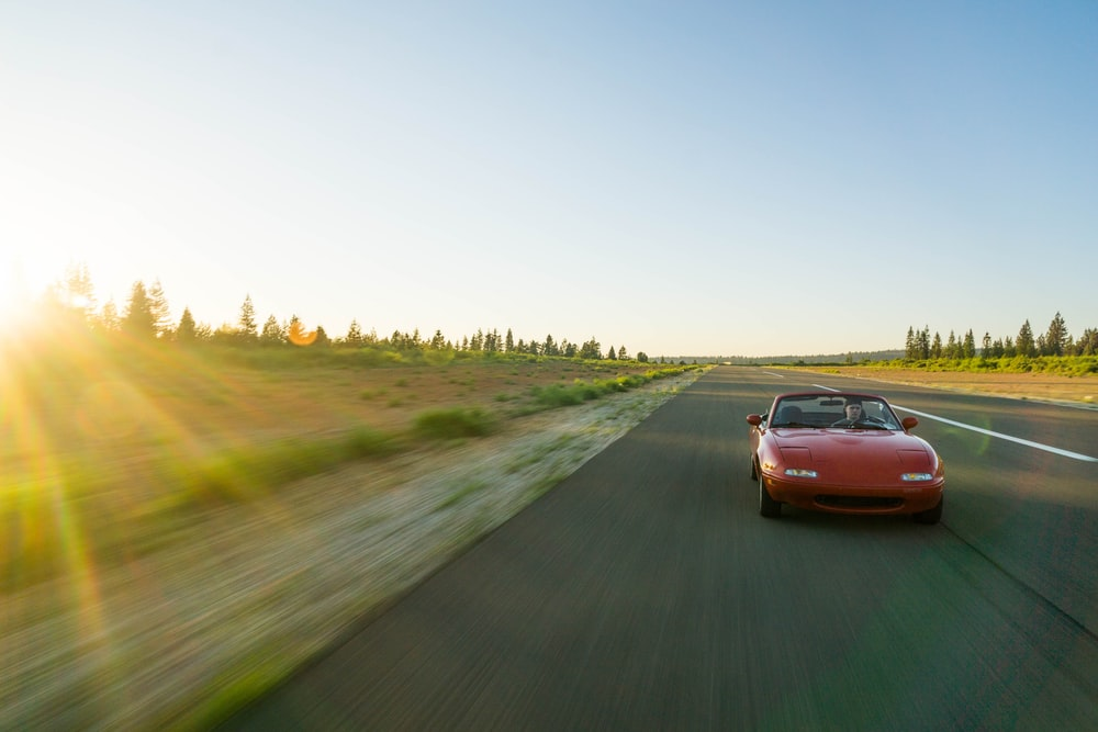 panning photography of red Mazda MX-5 Miata