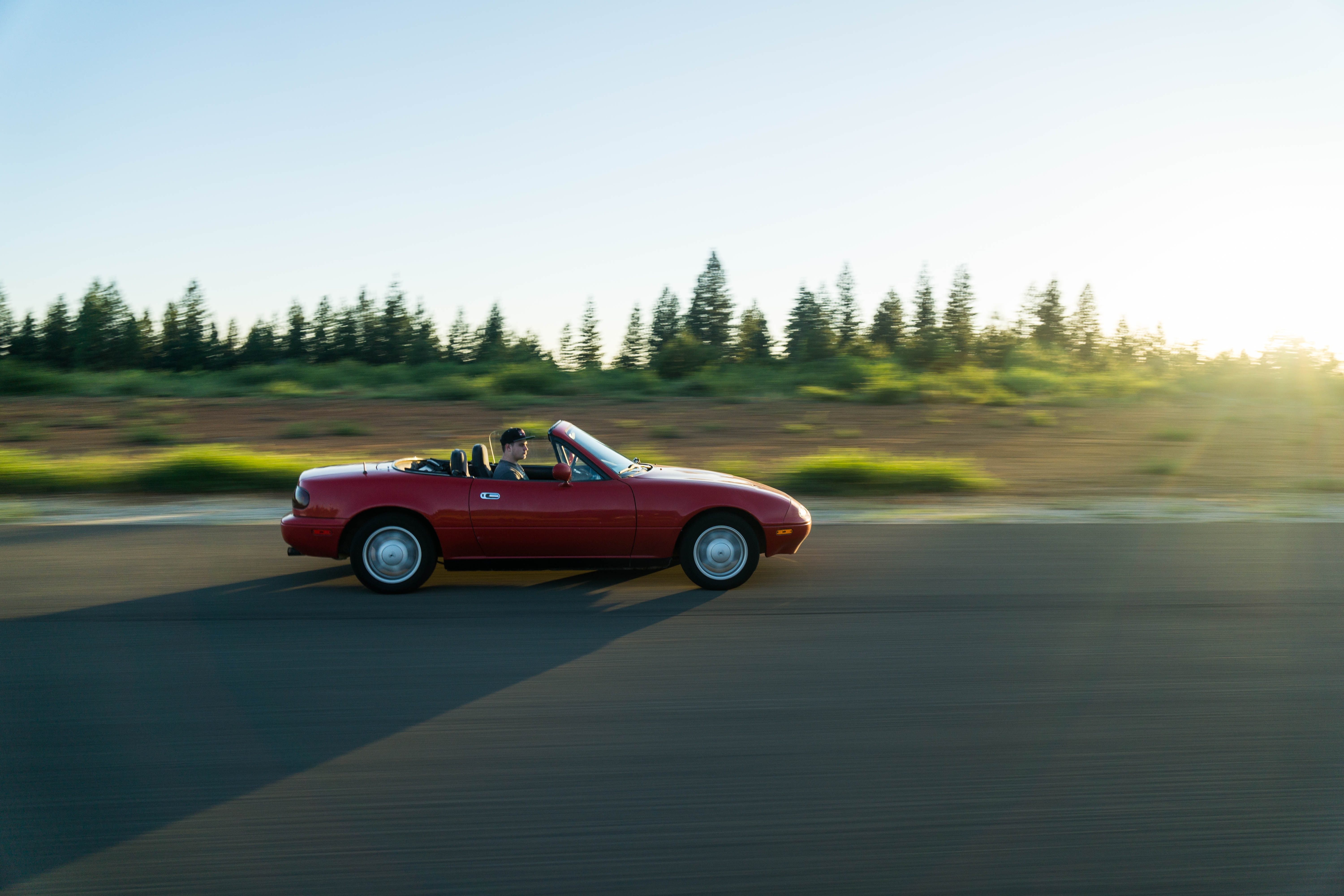 panning photography of man in red convertible