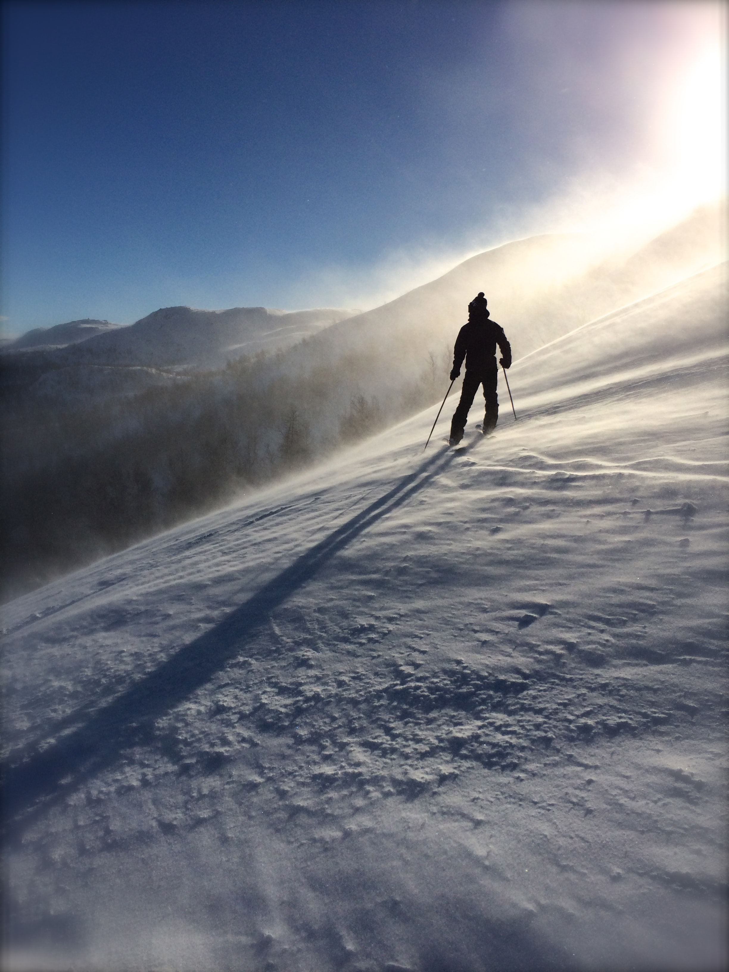 A silhouette of a skier going down a sunny snow slope