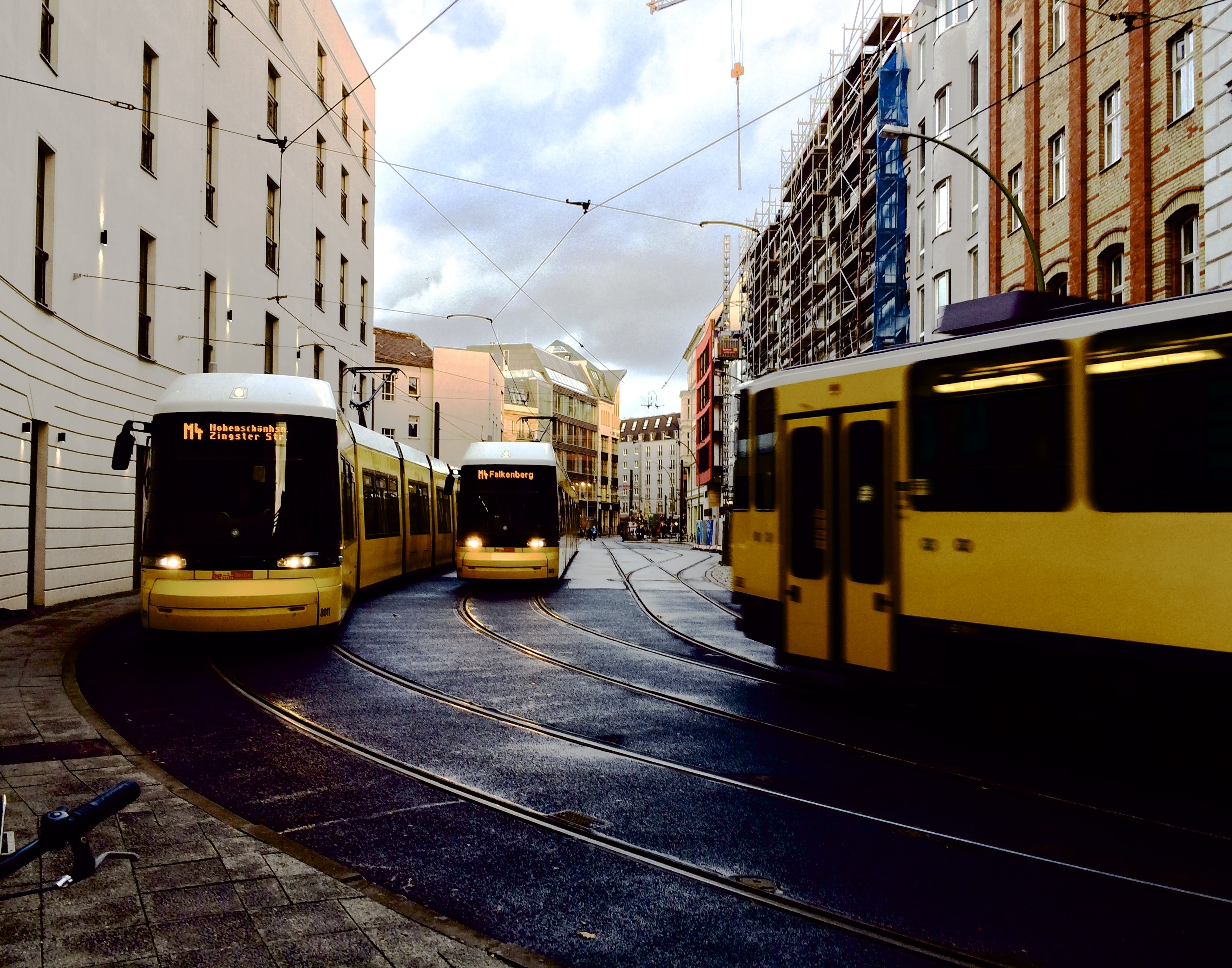 Yellow streetcars around the corner of a city street