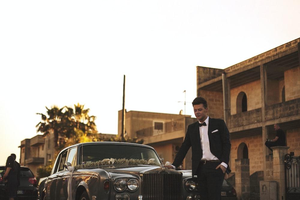 man wearing black suit jacket standing near gray car