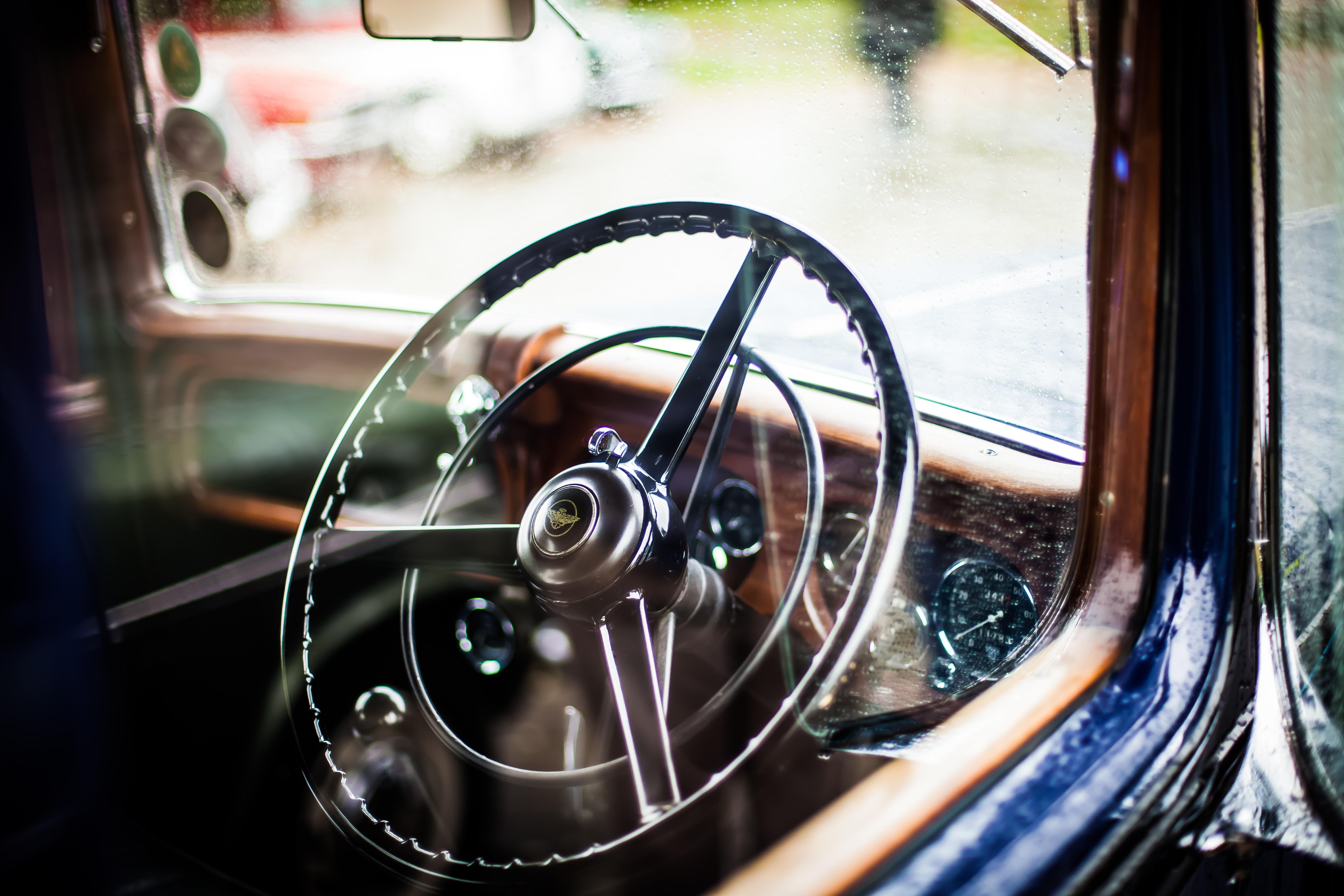 Vintage chrome steering wheel and dashboard seen through car window