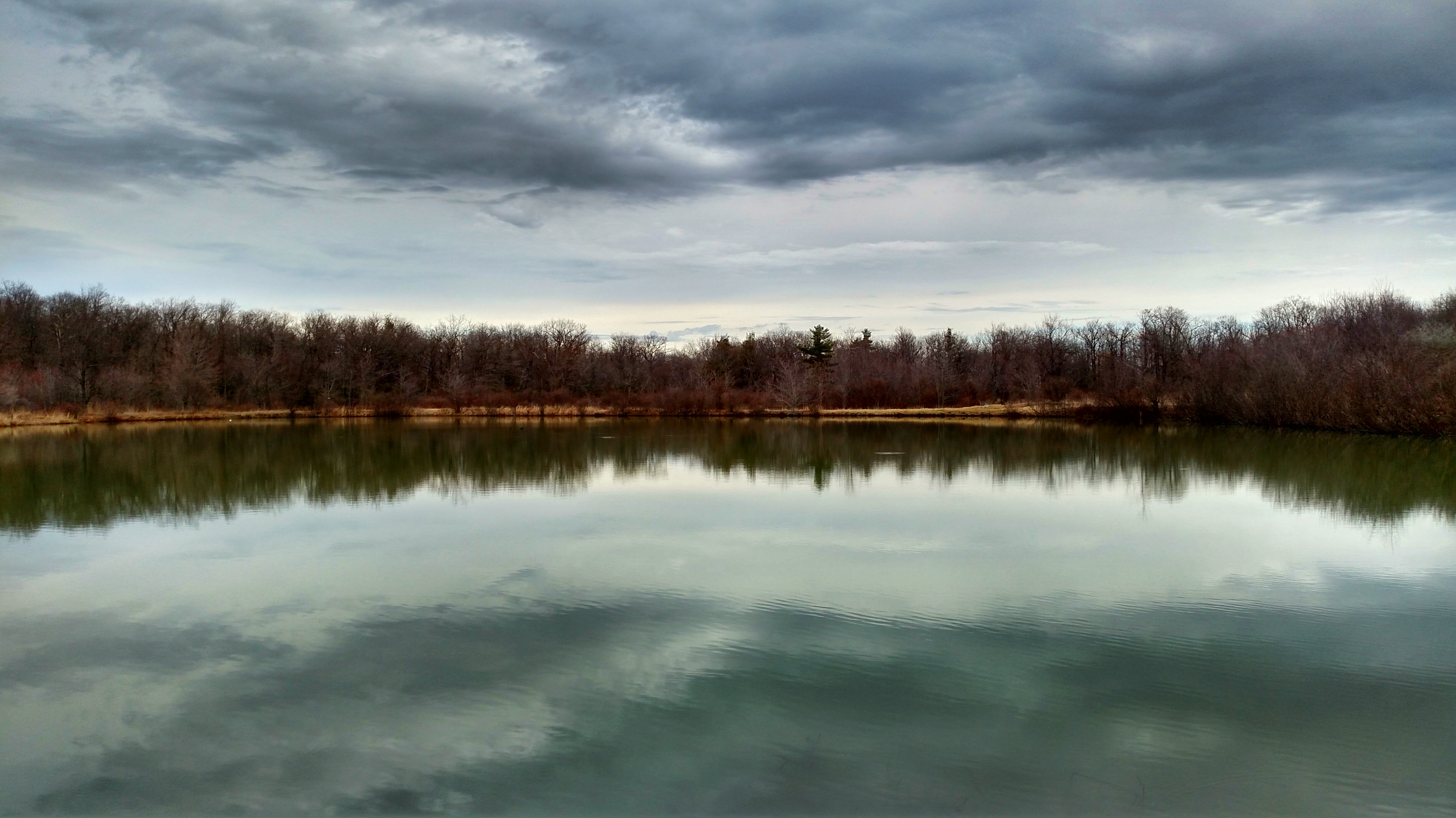 A smooth lake under heavy gray clouds in the autumn