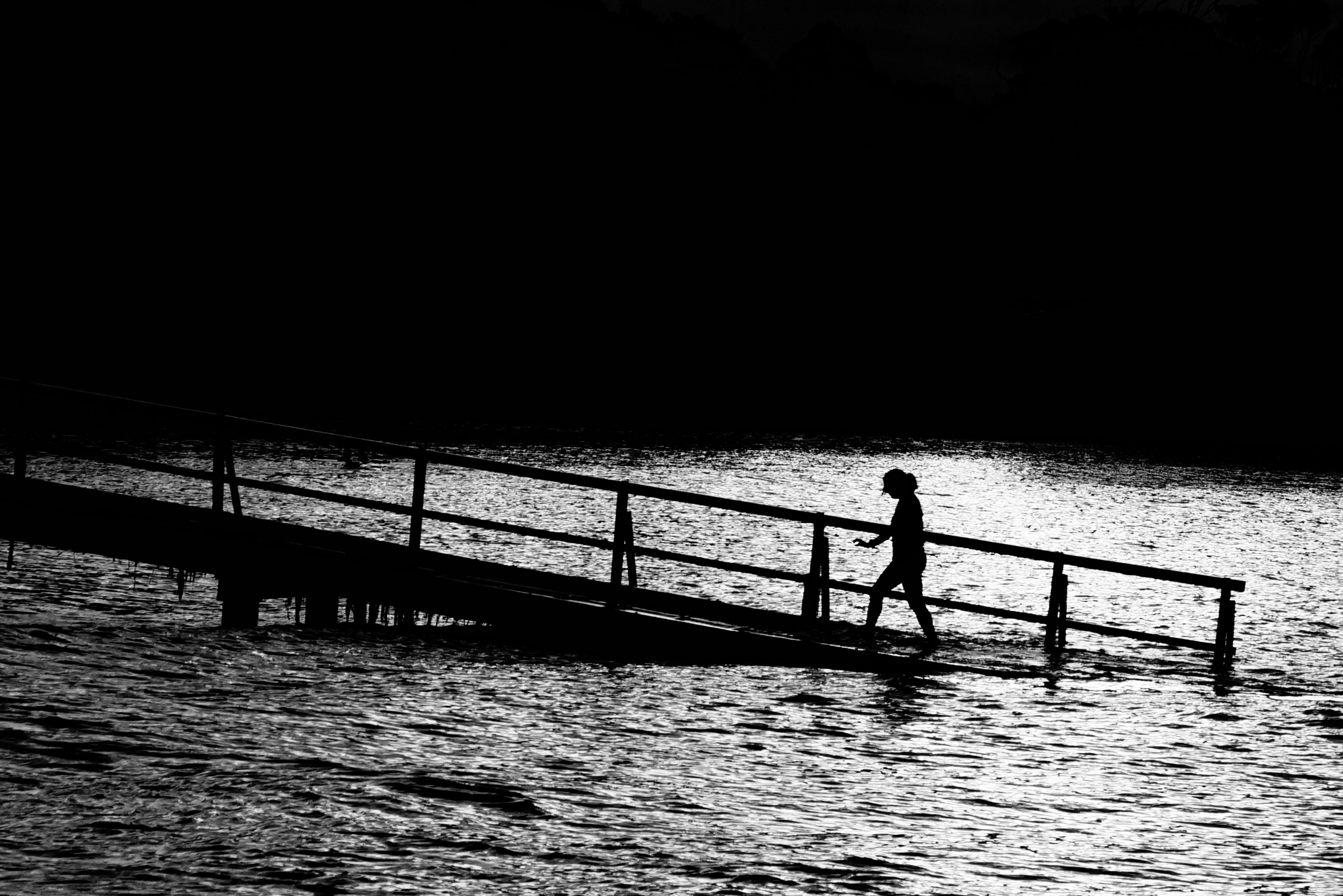 person walks on brown pier over body of water