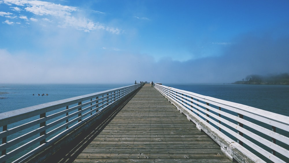 gray and white wooden sea dock under blue and white sky at daytime