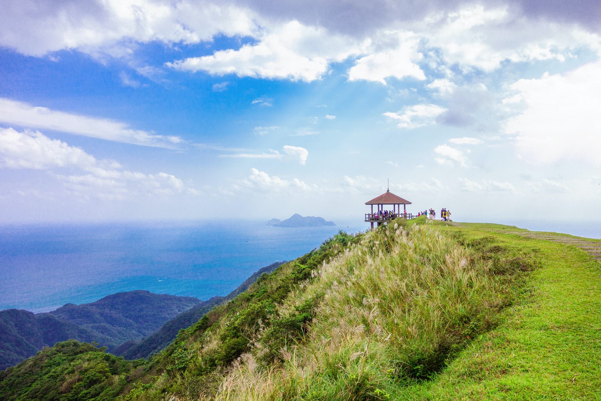 brown gazebo on top of green mountain overlooking sea during daytime landscape photography