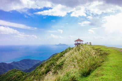 brown gazebo on top of green mountain overlooking sea during daytime landscape photography view zoom background