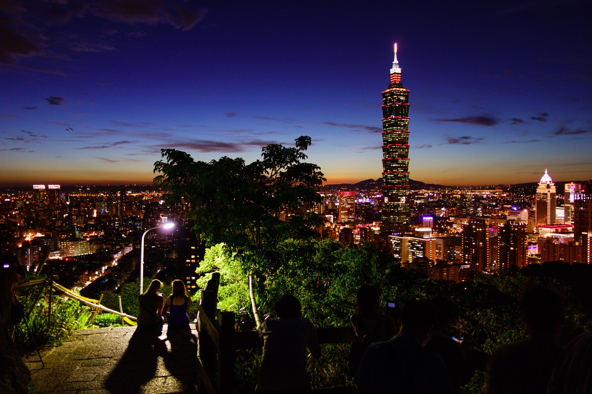 People on top of a hill admiring the Taipei cityscape and Taipei 101 skyscraper at night