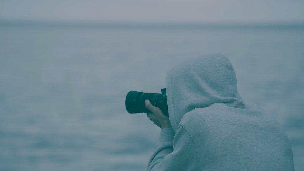 person wearing hoodie holding camera taking photo near body of water during daytime