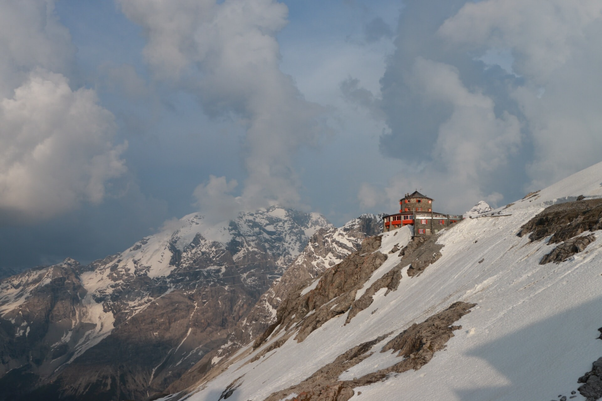 A building touches the clouds on top of a snow covered, rocky mountain
