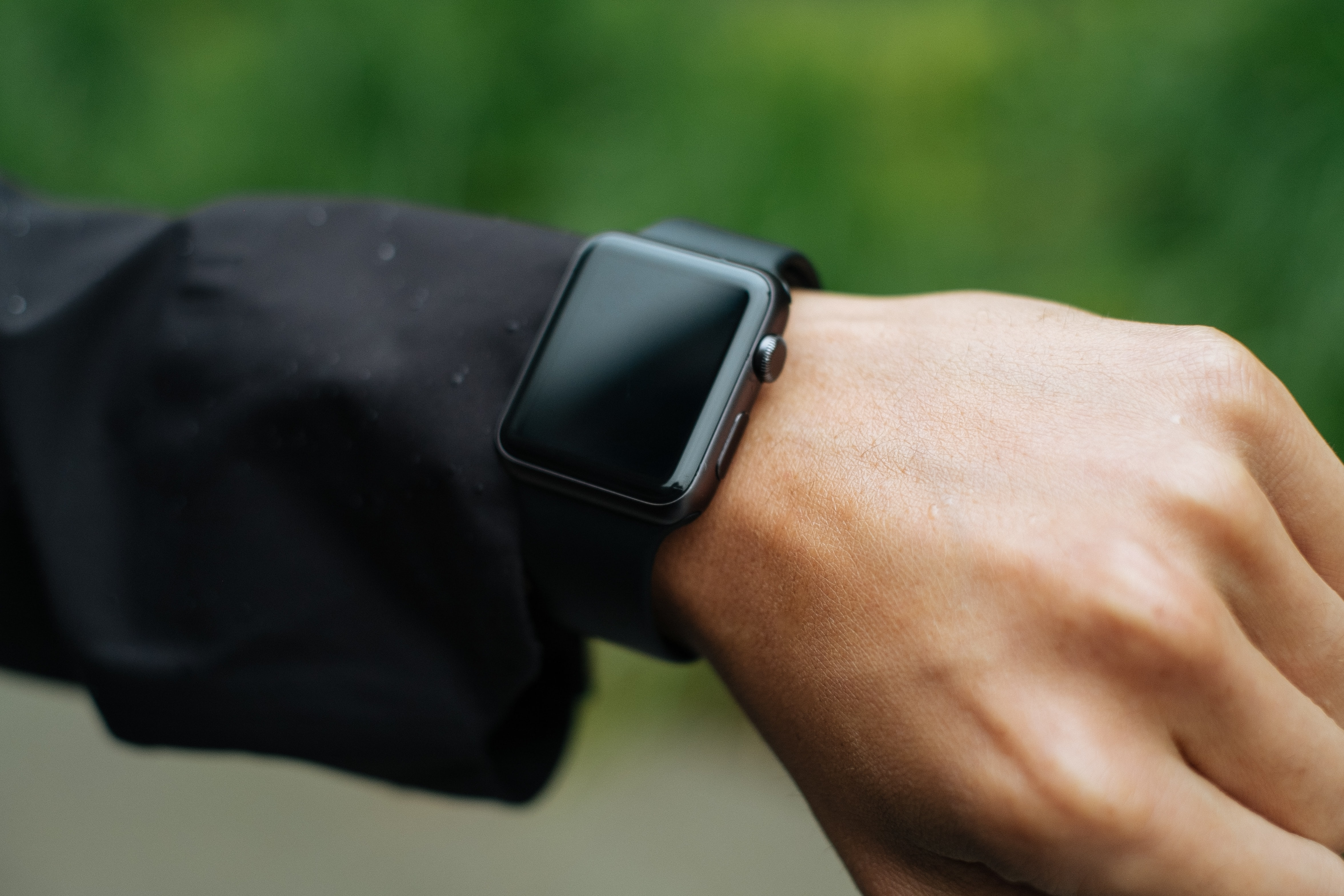 A close-up of an Apple Watch and raindrops on a man's arm.