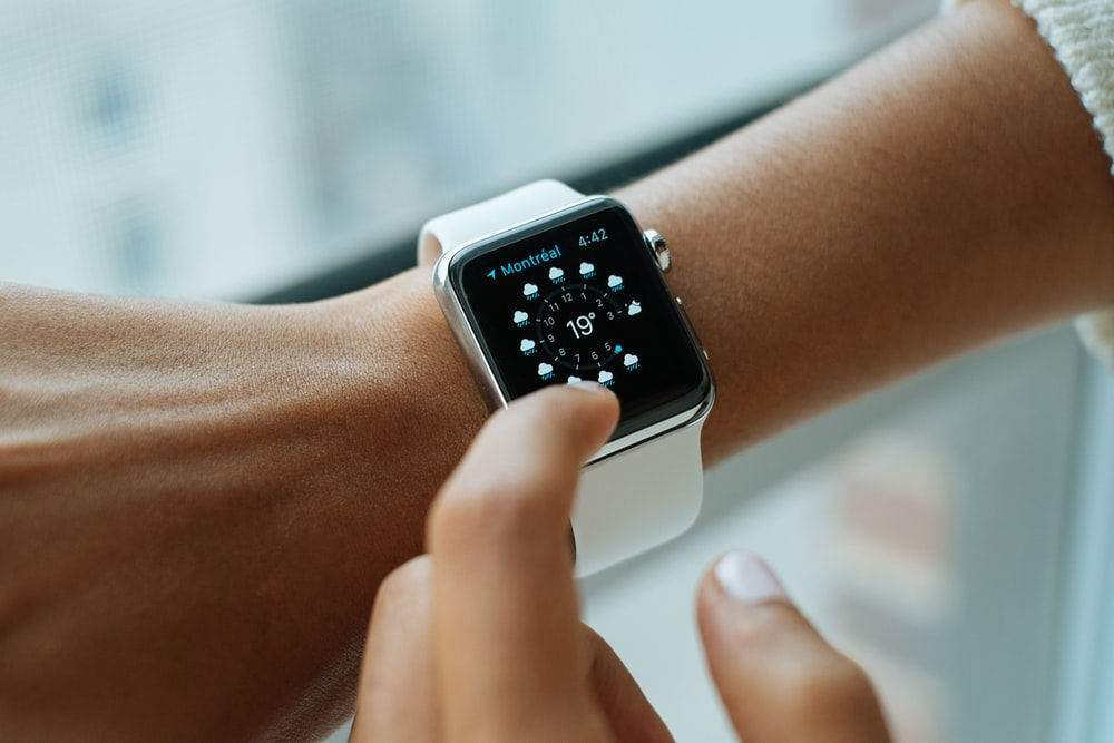 person wearing silver aluminium case Apple Watch with white Sports Band