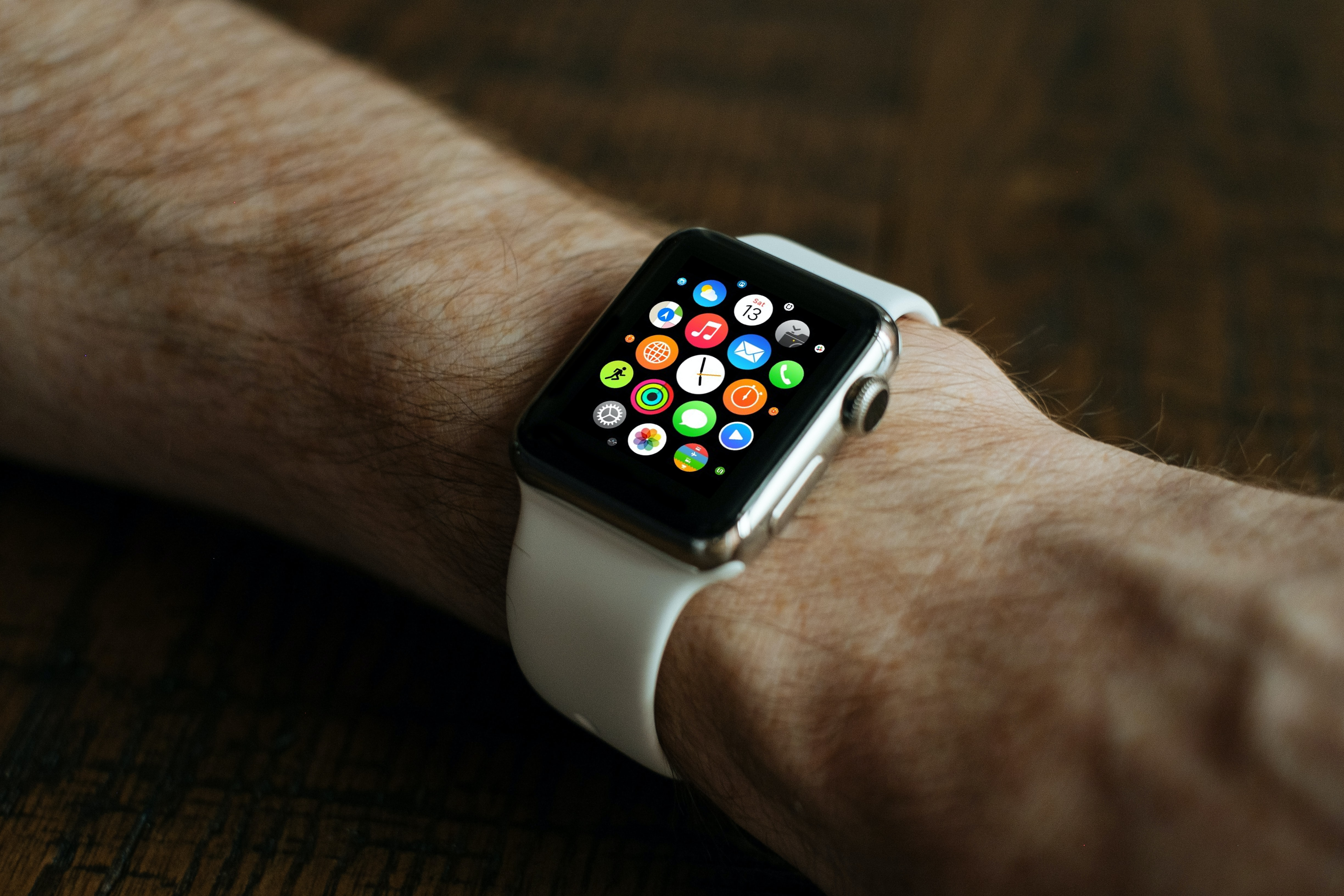 A man with a hairy arm wearing an Apple watch on its home screen with a white band